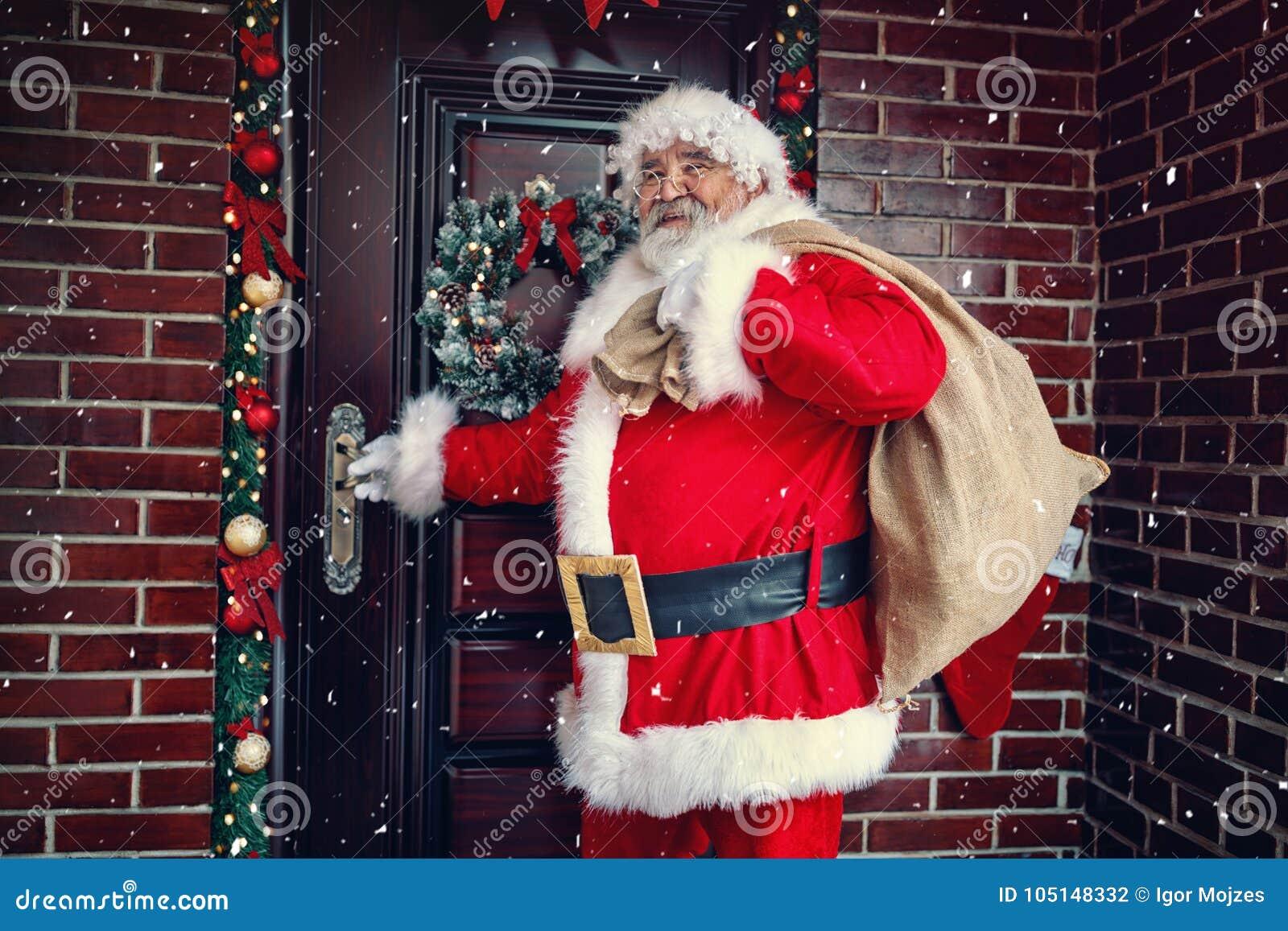 Szczęśliwy Święty Mikołaj przyjeżdża z teraźniejszością na wielkiej torbie w przy nocą