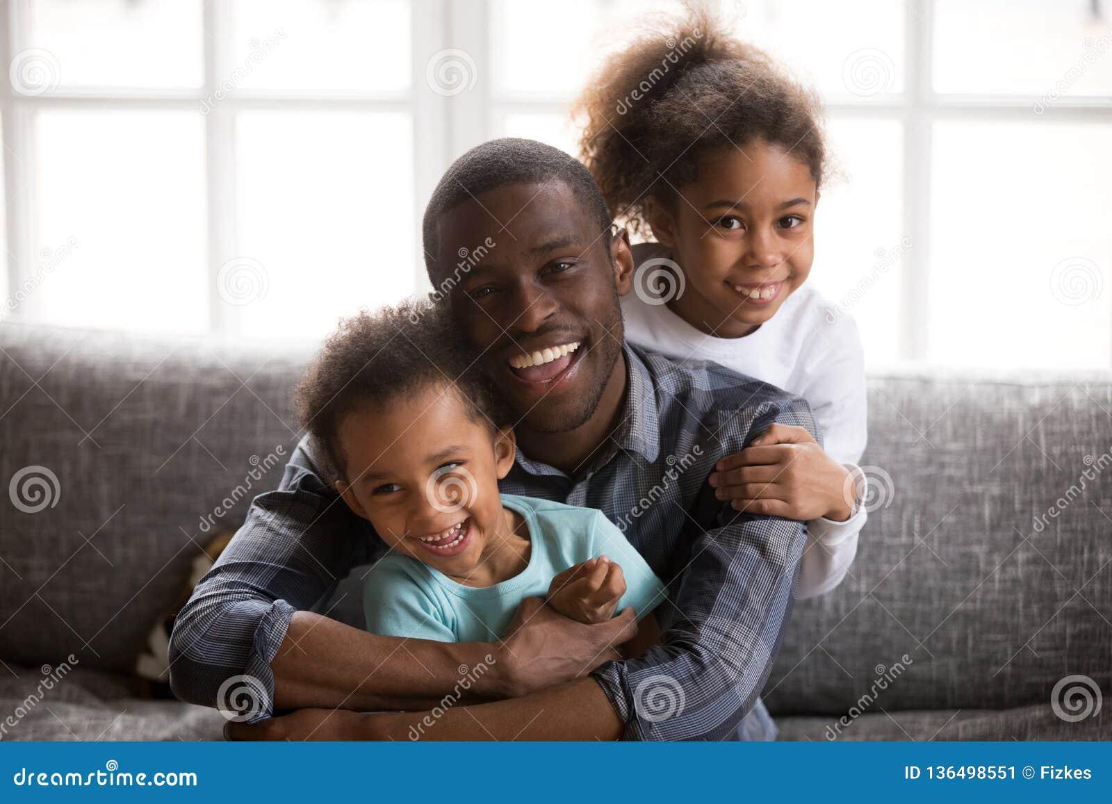 Szczęśliwy afrykański tata i mieszający biegowy dziecko portret w domu