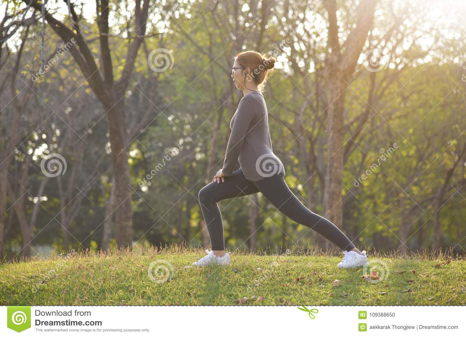 Szczęśliwy Azjatycki żeński trening przy parkiem
