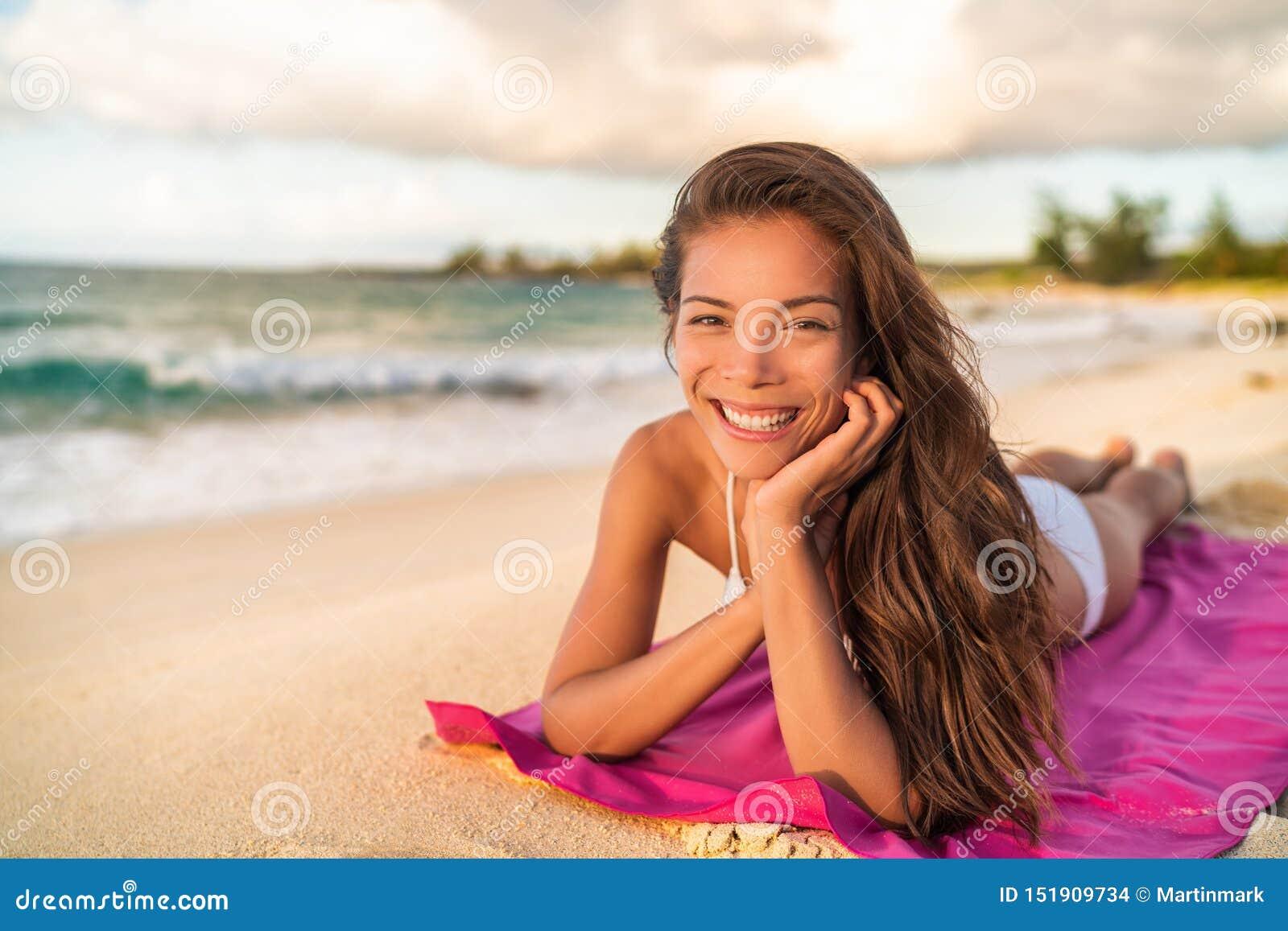 Szczęśliwy Azjatycki bikini wwoman model relaksuje na wakacje lying on the beach na plażowym ręczniku, Hawaje