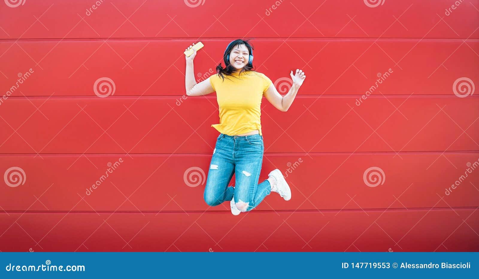 Szczęśliwy Azjatycki dziewczyny doskakiwanie podczas gdy słuchający muzyczny plenerowego - Szalona Chińska kobieta ma zabawę tanc