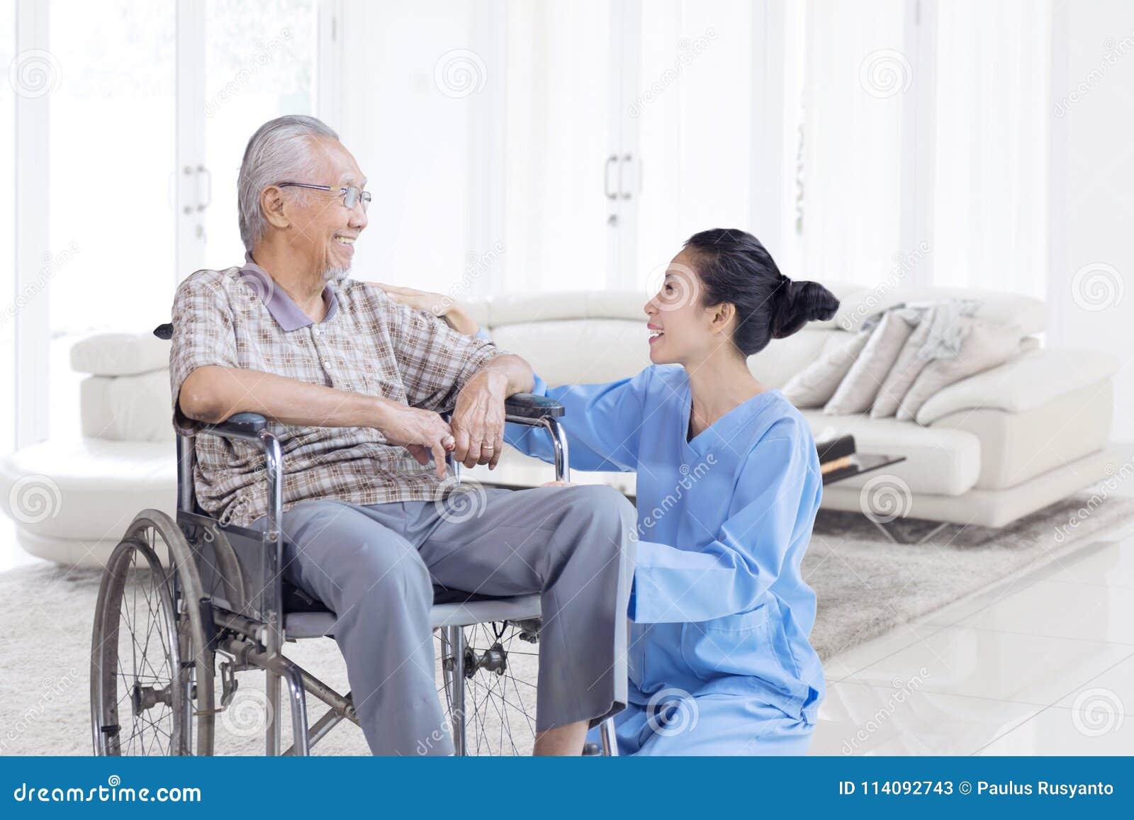 Szczęśliwy Azjatycki starsza osoba mężczyzna opowiada z pielęgniarką