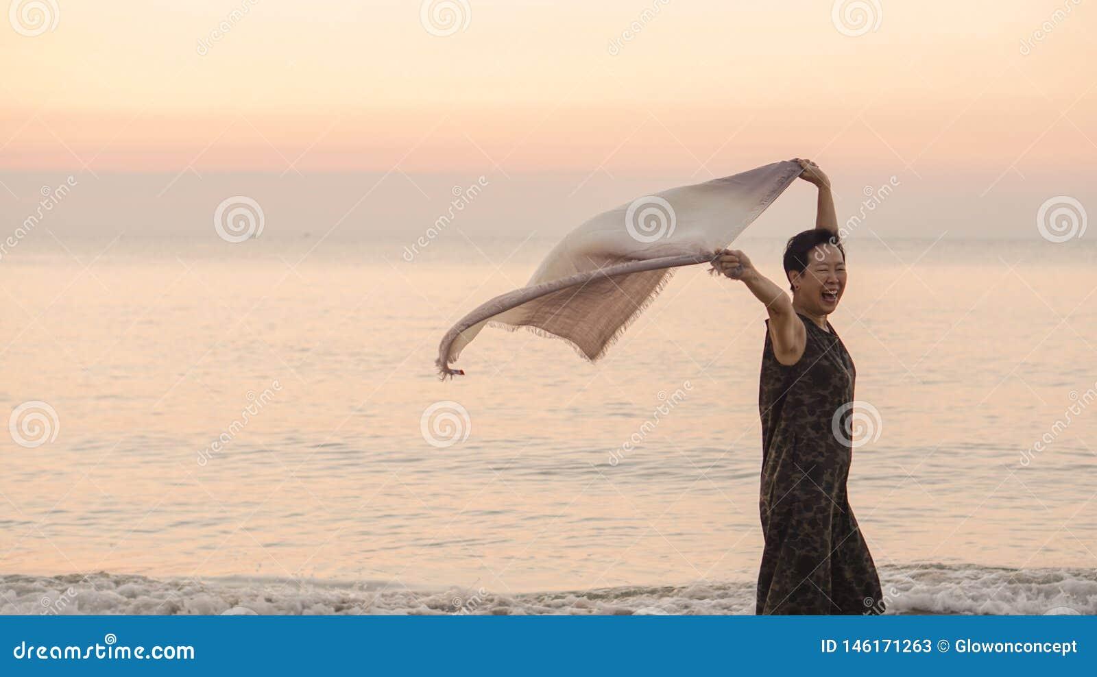 Szczęśliwy Azjatycki starszy kobiety tun przy plażą z szalik tkaniną i kopii przestrzenią