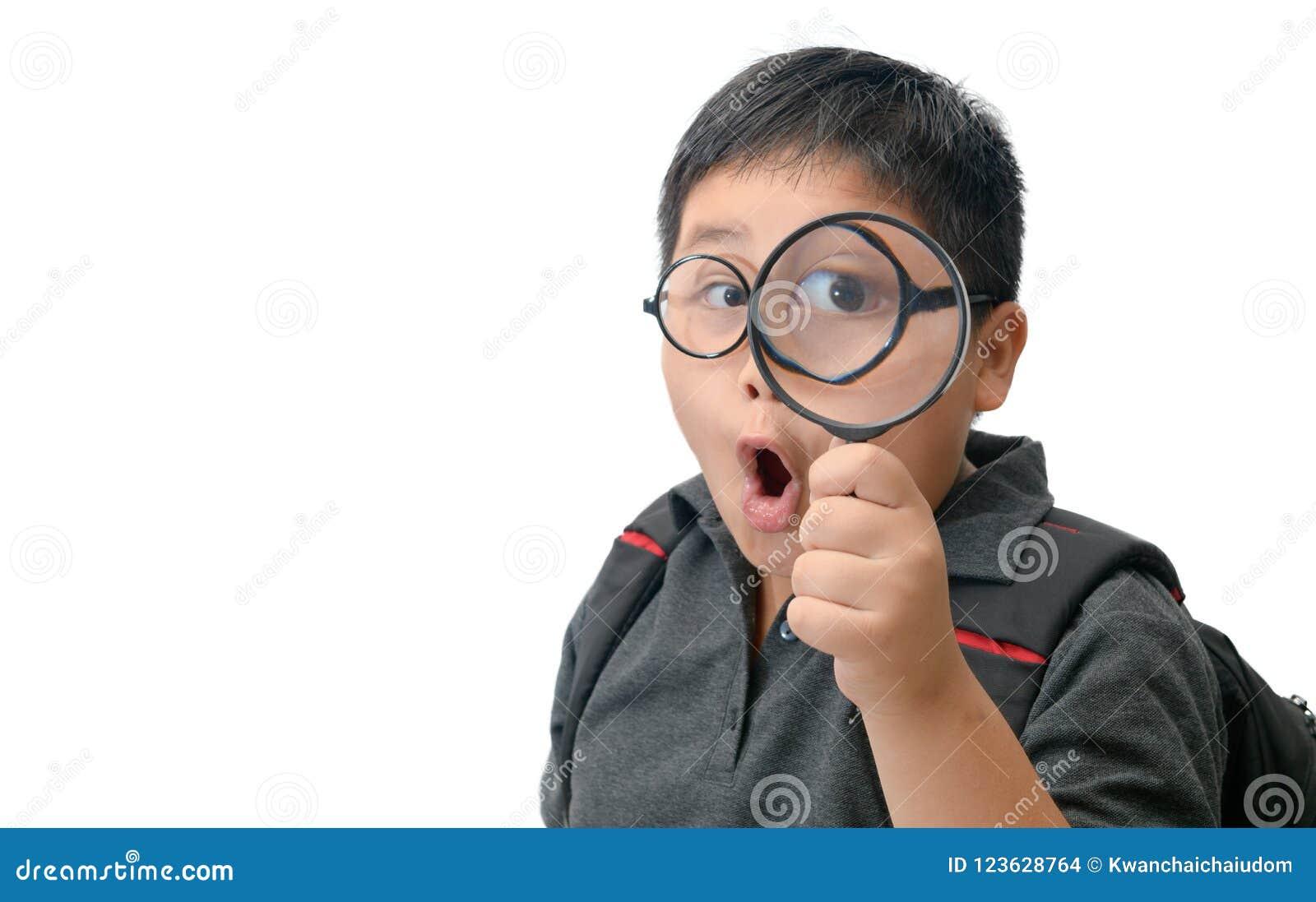 Szczęśliwy azjatykci gruby chłopiec mienia powiększać - szkło