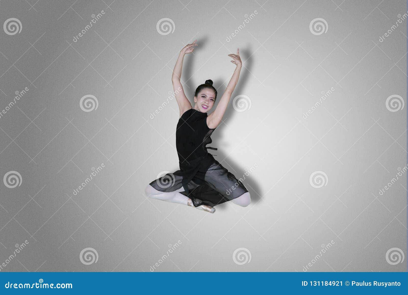 Szczęśliwy baletniczy tancerz wykonuje eleganckiego skok