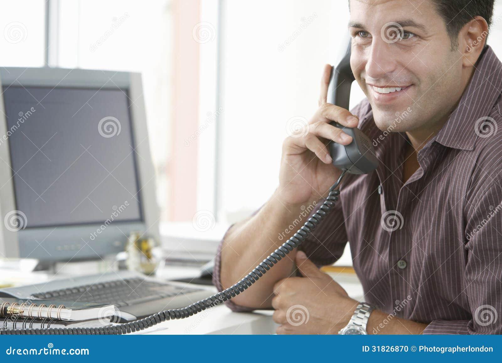 Szczęśliwy biznesmen Używa kabla naziemnego telefon W biurze