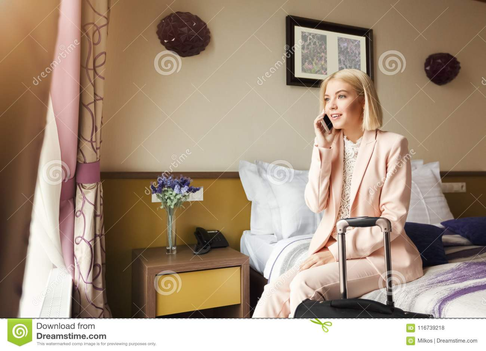 Szczęśliwy biznesowej kobiety obsiadanie w pokoju hotelowym