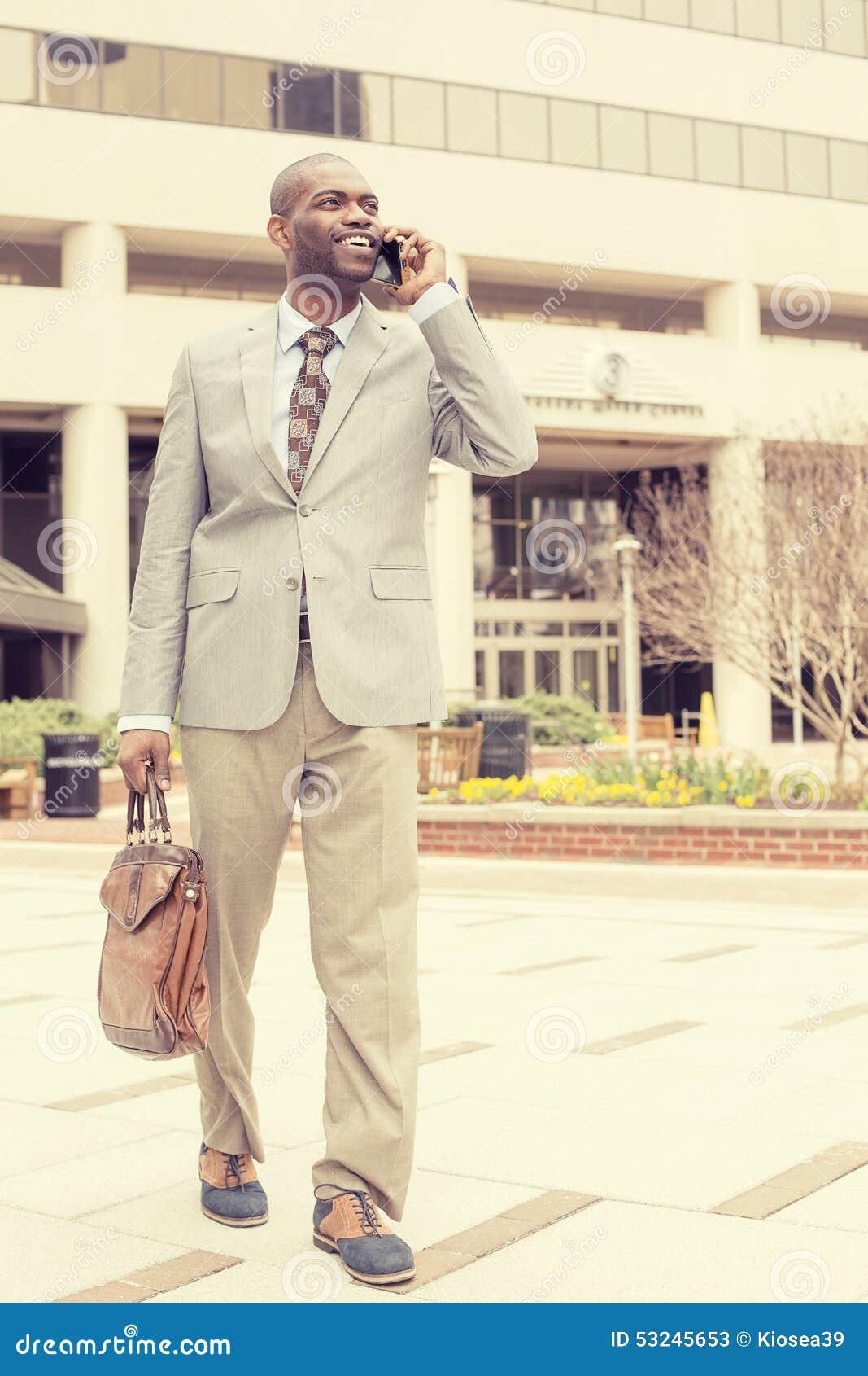 Szczęśliwy biznesowy mężczyzna opowiada na jego telefonie podczas gdy chodzący outside