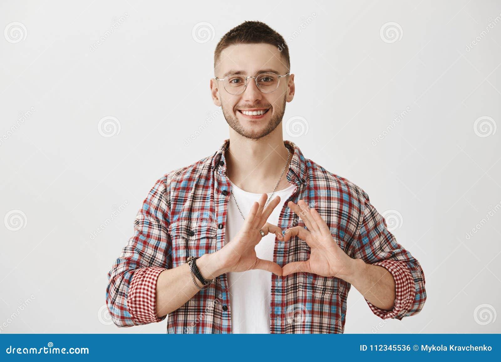 Szczęśliwy być w miłości z tobą Studio strzał atrakcyjny zwyczajny facet w szkłach pokazuje serce podpisuje klatkę piersiową, ono