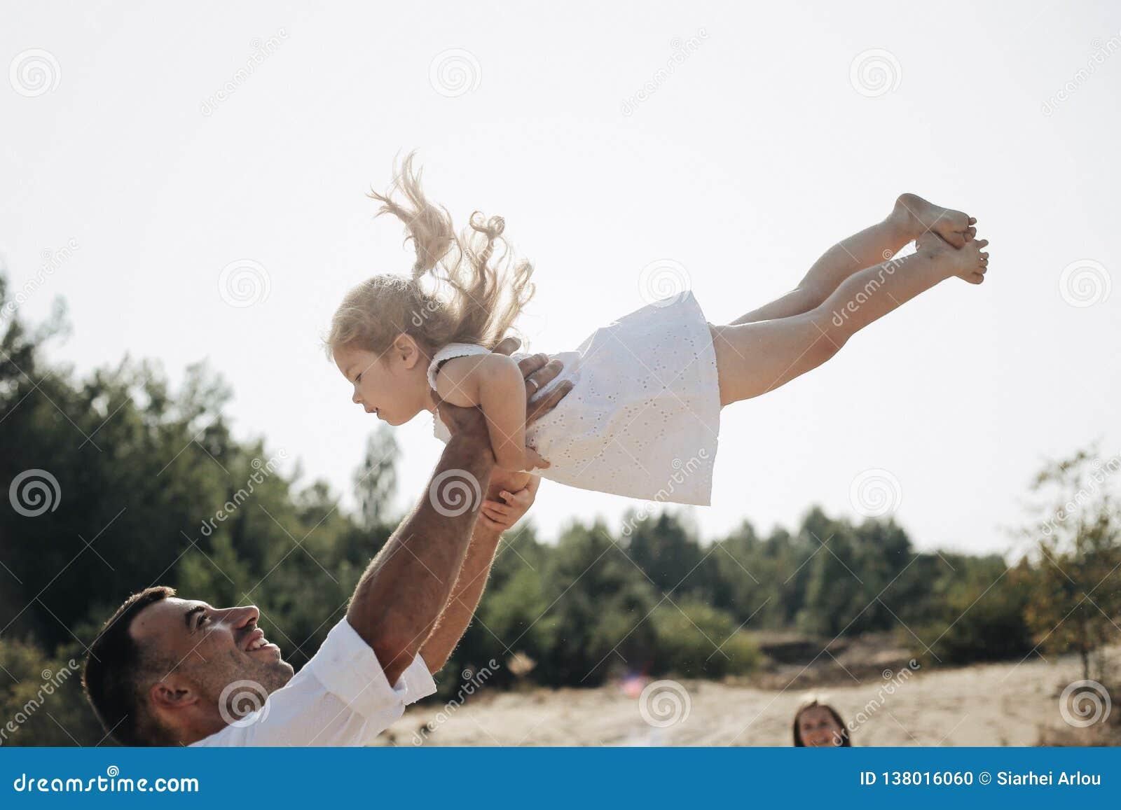 Szczęśliwy caucasian tata i jego mała córka ma zabawę Ojciec rzuca słodkiej córki w biel sukni w powietrzu