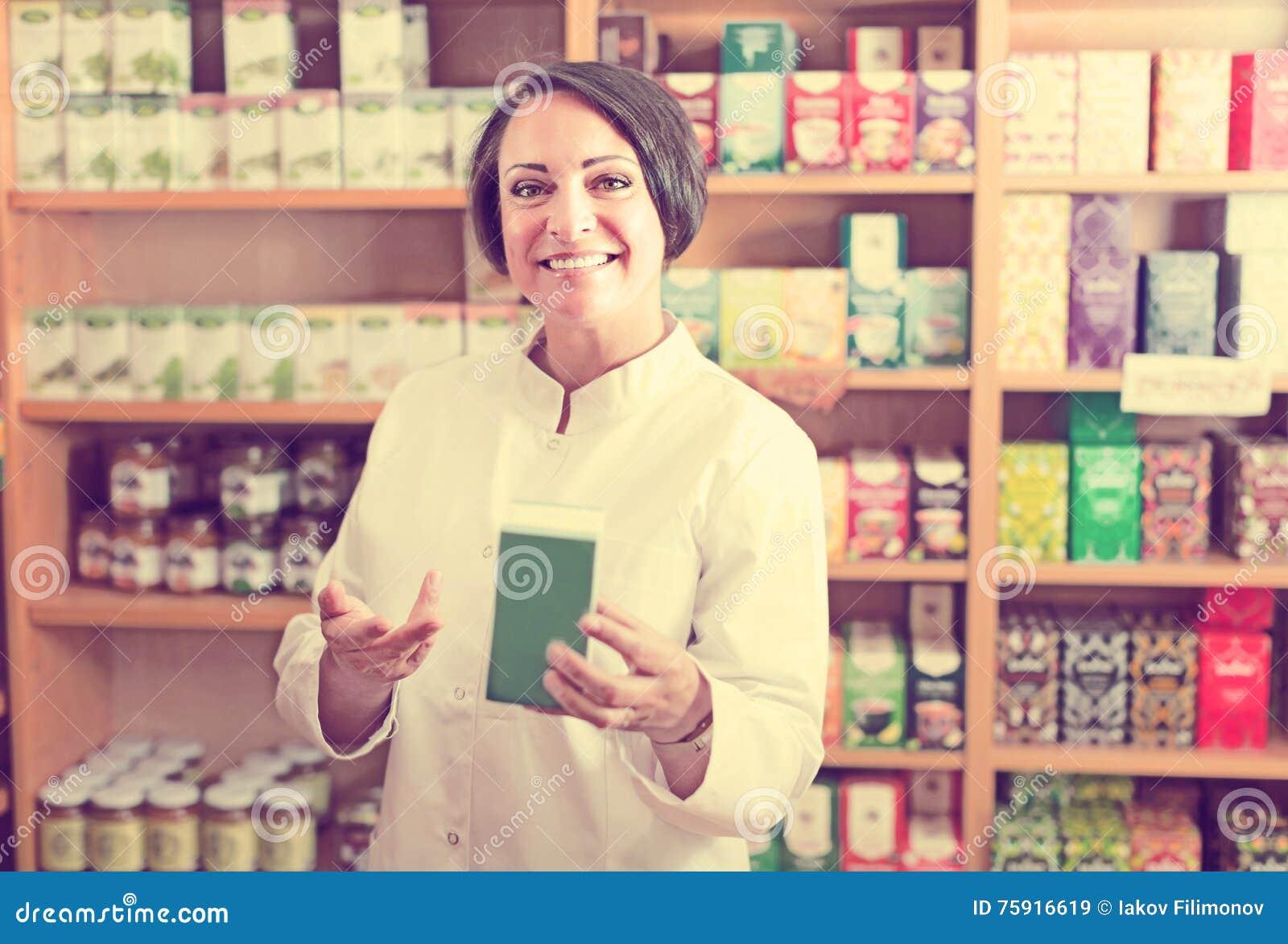 Szczęśliwy dojrzały żeński sprzedawca trzyma żywienioniowe odżywki