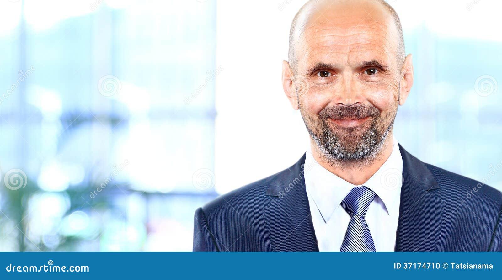 Szczęśliwy dojrzały biznesowy mężczyzna patrzeje kamerę