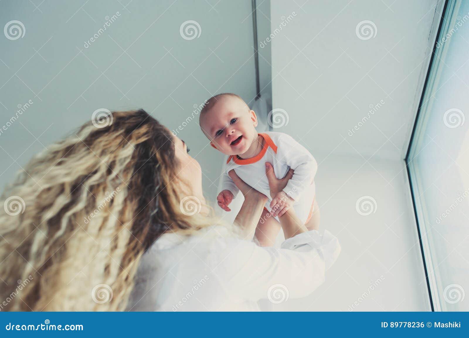 Szczęśliwy dom rodzinny Macierzysty mienia dziecka syn w sypialni w wygodnym weekendzie