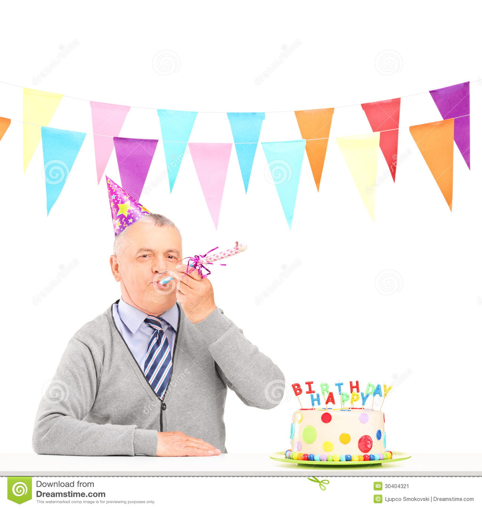 Szczęśliwy dorośleć mężczyzna z partyjnym kapeluszowym dmuchaniem i urodzinowym tortem