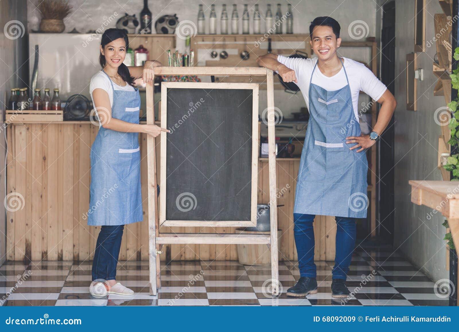 Szczęśliwy dwa małych biznesów właściciel przygotowywający otwierać ich kawiarni