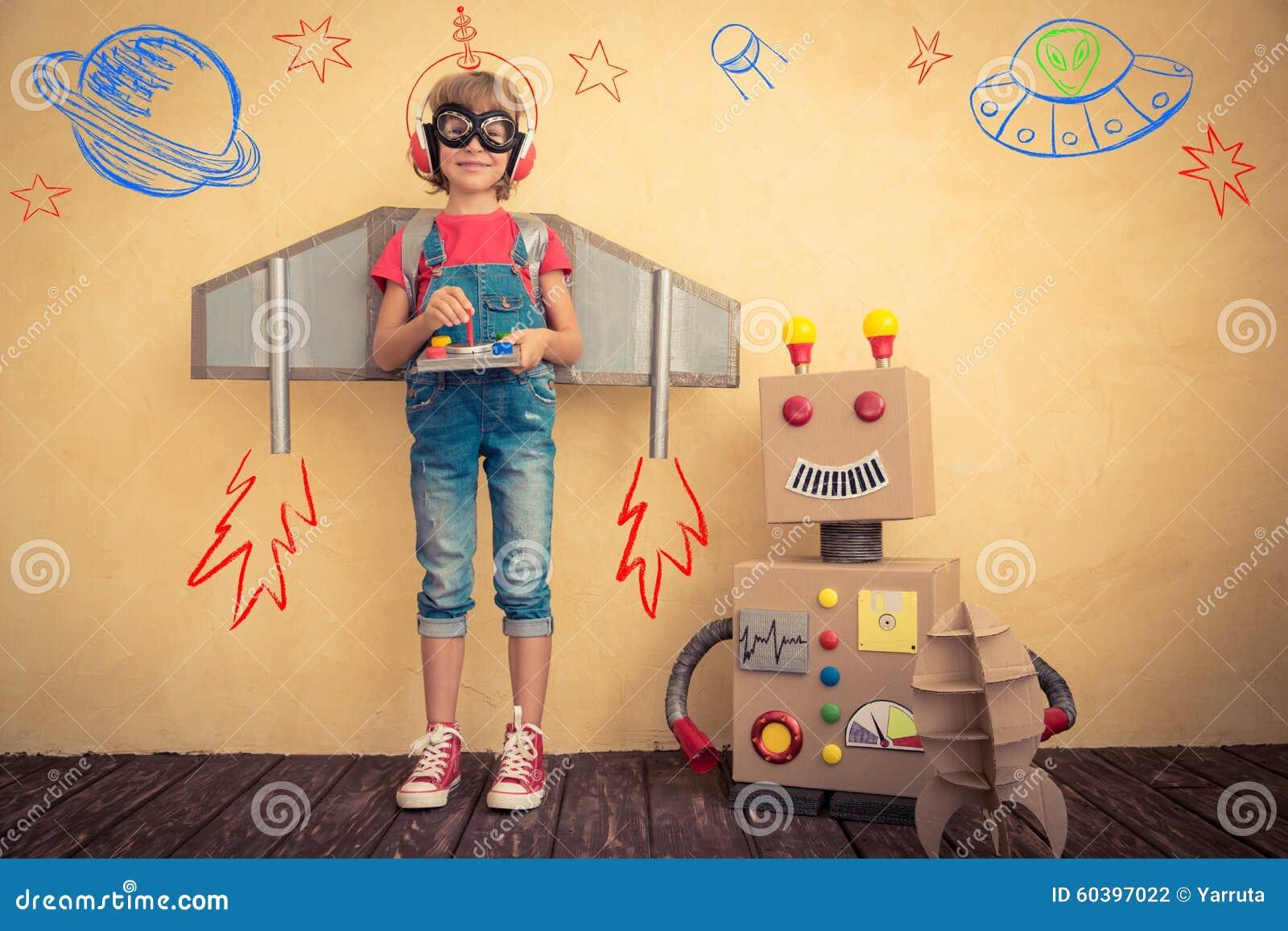 Szczęśliwy dzieciak bawić się z zabawkarskim robotem