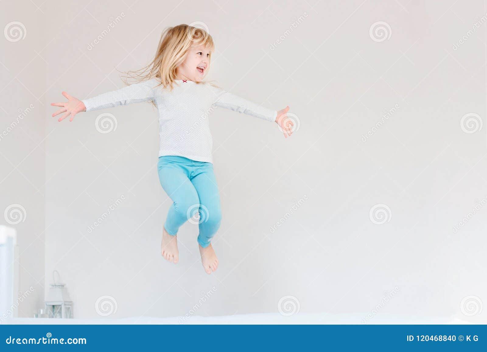 Szczęśliwy dzieciak skacze nad łóżkiem Śliczna mała blond dziewczyna ma zabawę indoors Szczęśliwy i niestaranny dzieciństwa pojęc