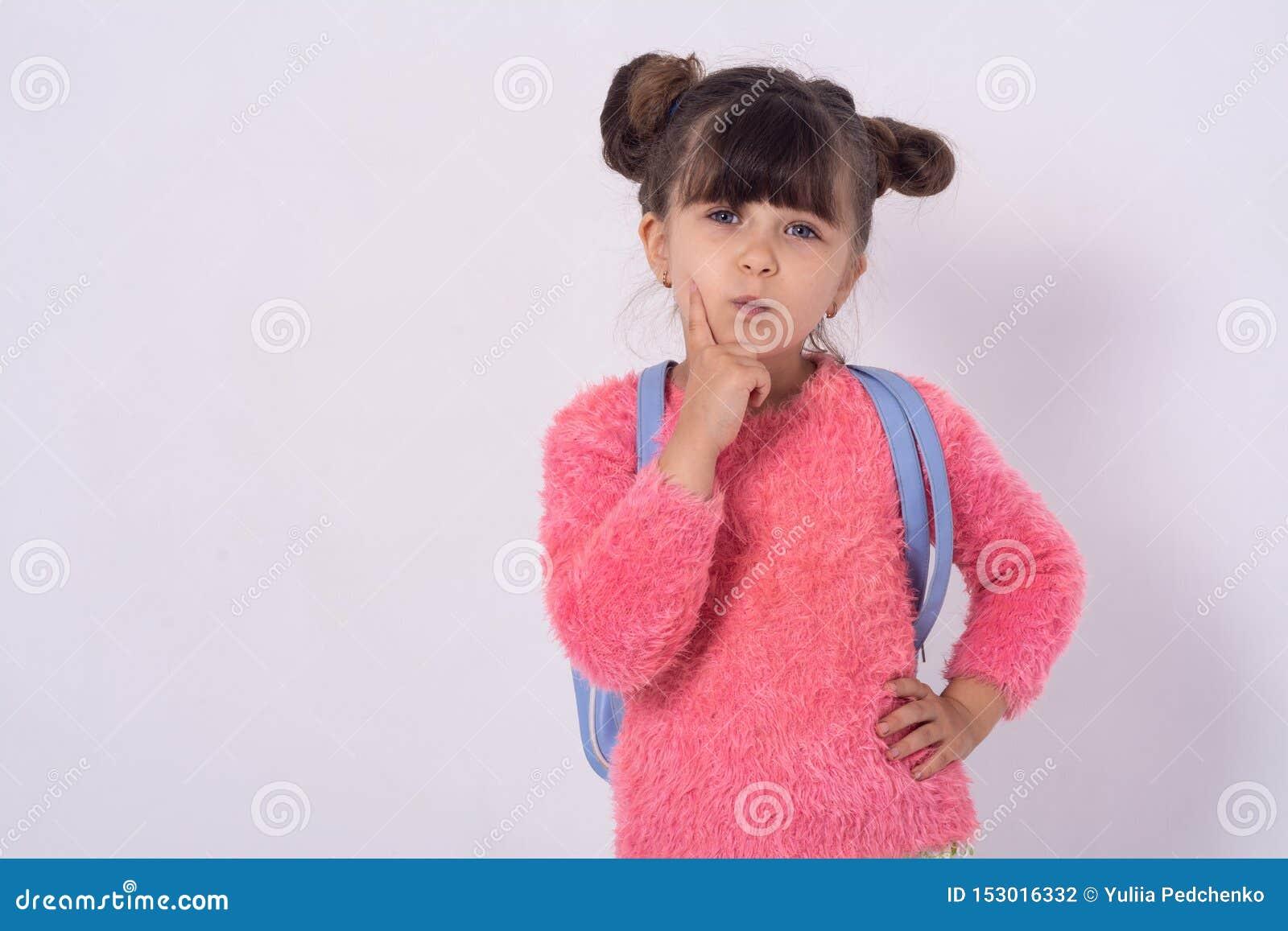 Szczęśliwy dzieciak z schoolbag myśleć na białym tle Szkolny dzieciak gotowy dla szkoły