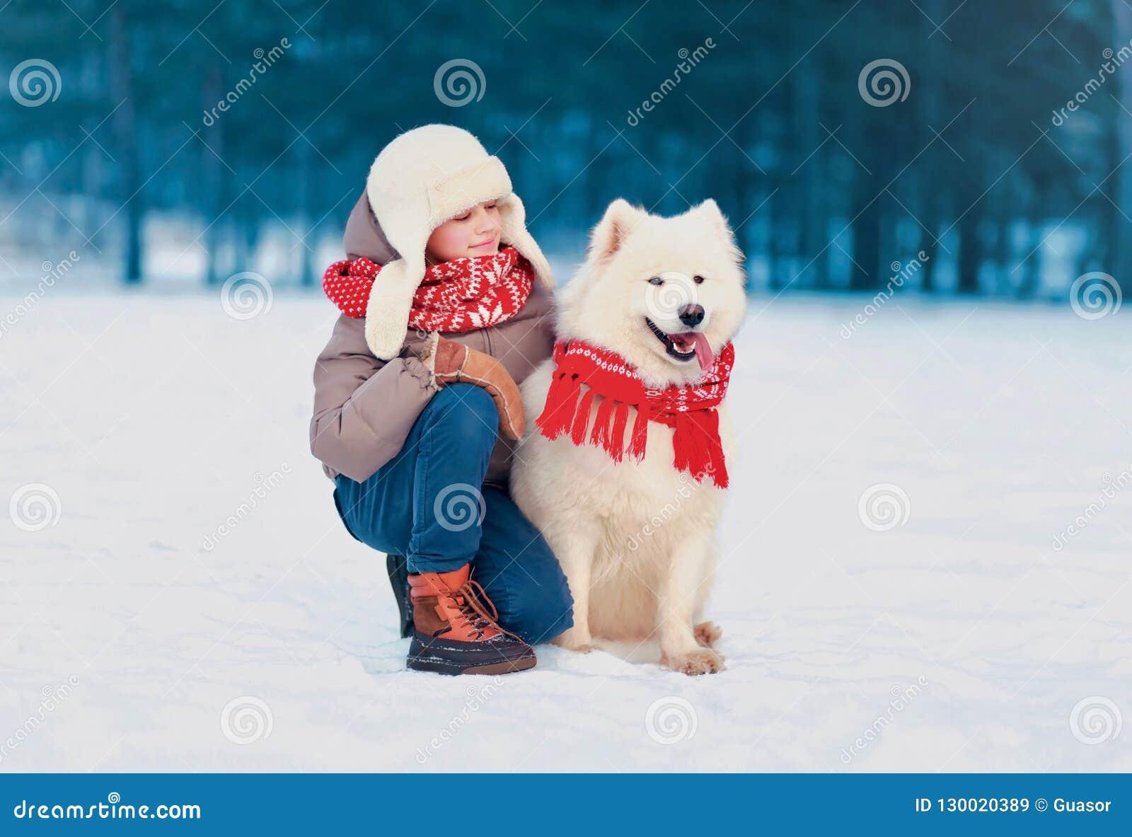 Szczęśliwy dziecka obsiadanie z jego białym Samoyed psem w zima dniu