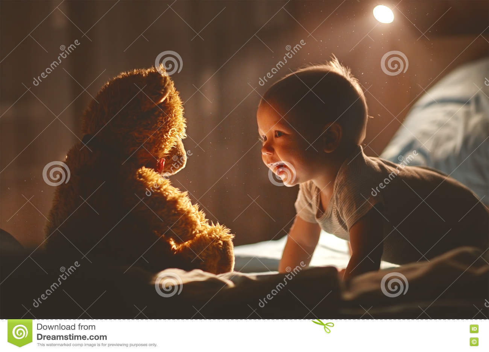 Szczęśliwy dziecko śmia się z misiem w łóżku