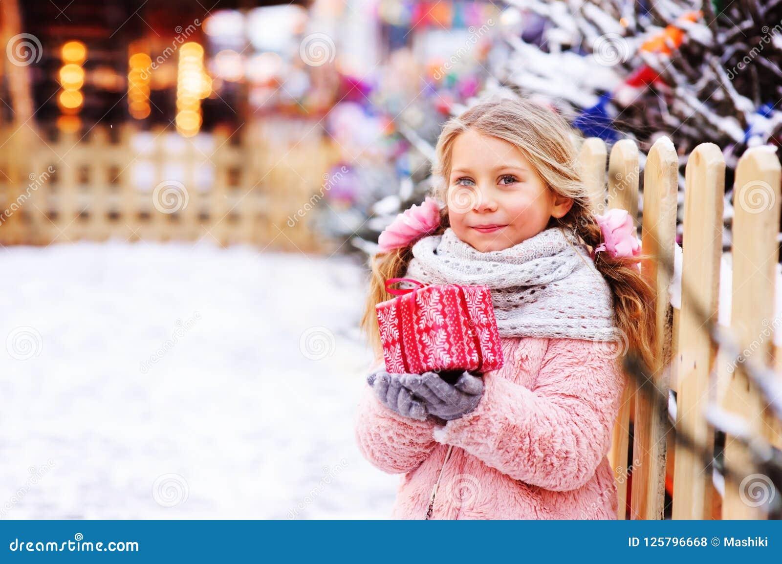 Szczęśliwy dziecko dziewczyny mienia bożych narodzeń prezent plenerowy na spacerze w śnieżnym zimy mieście