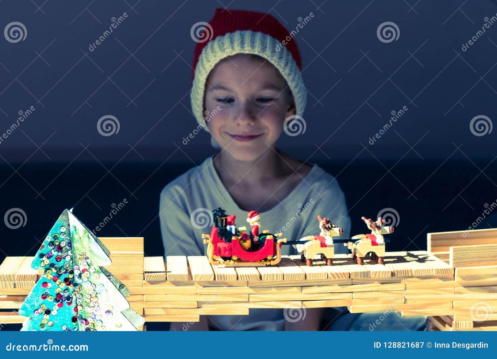 Szczęśliwy dziecko patrzeje Santa ` s sanie w Santa's budzie