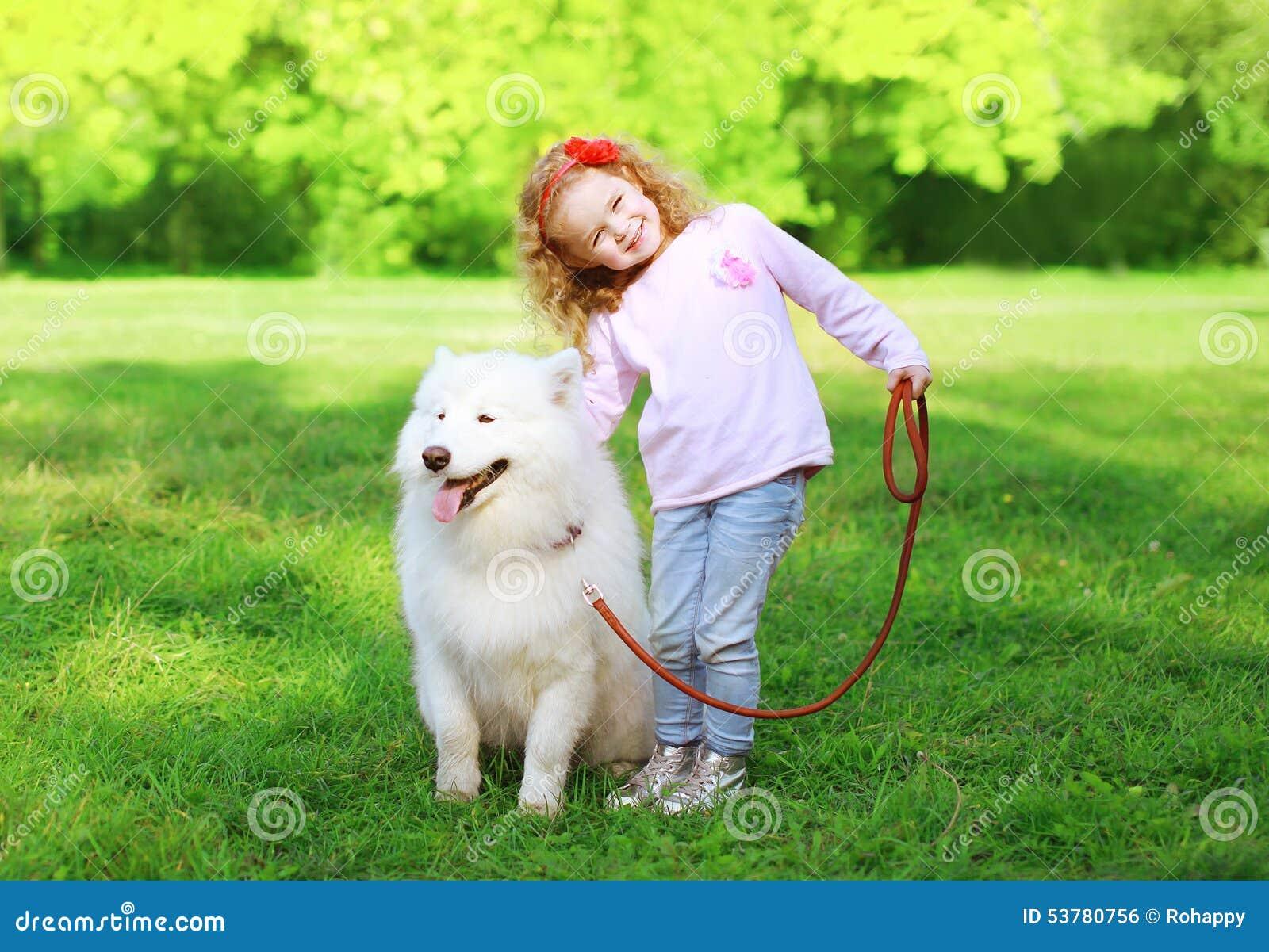 Szczęśliwy dziecko z białym Samoyed psem na trawie