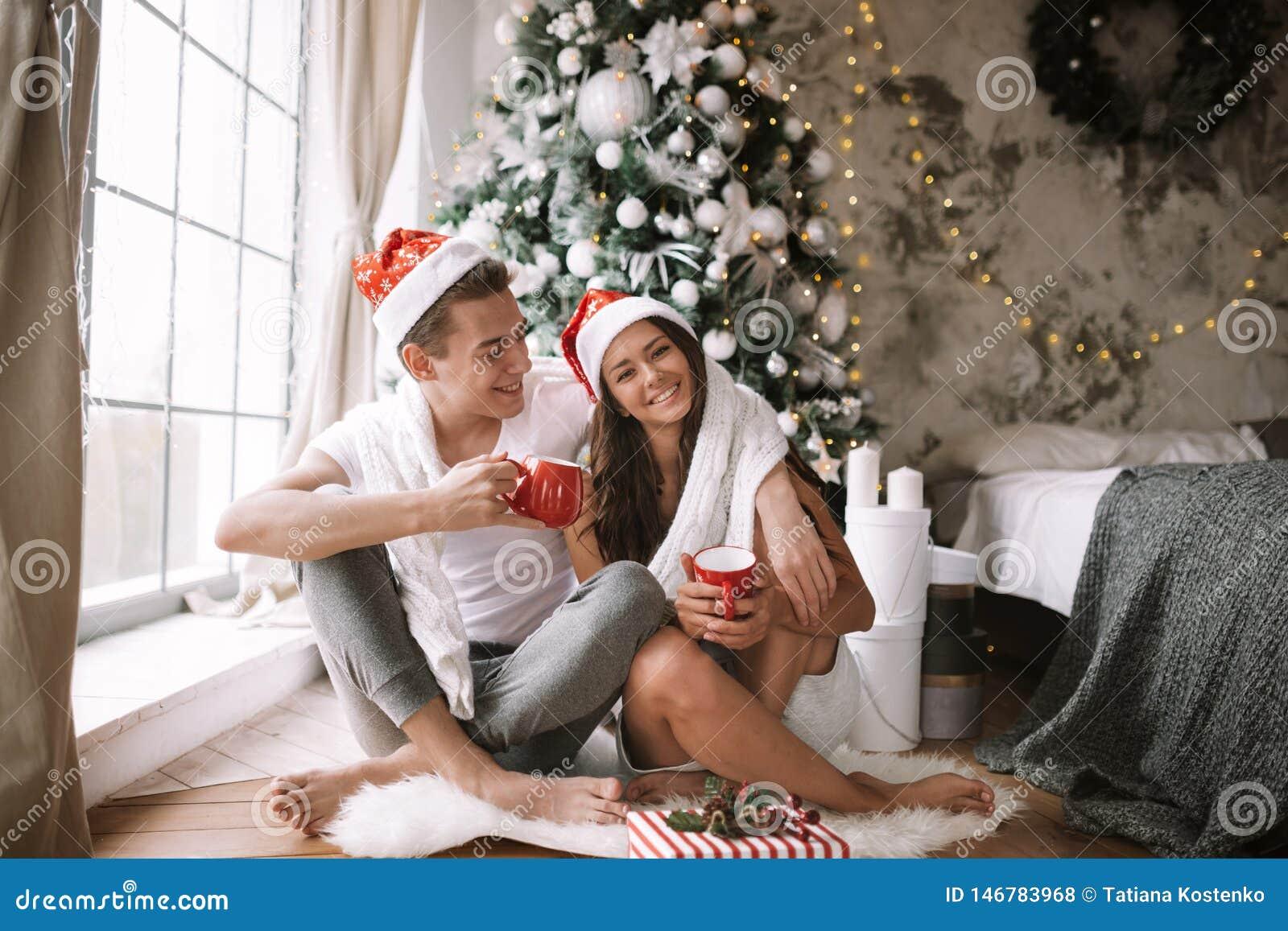 Szczęśliwy facet i dziewczyna w białych Święty Mikołaj kapeluszach i koszulkach siedzimy z czerwonymi filiżankami na podłodze prz