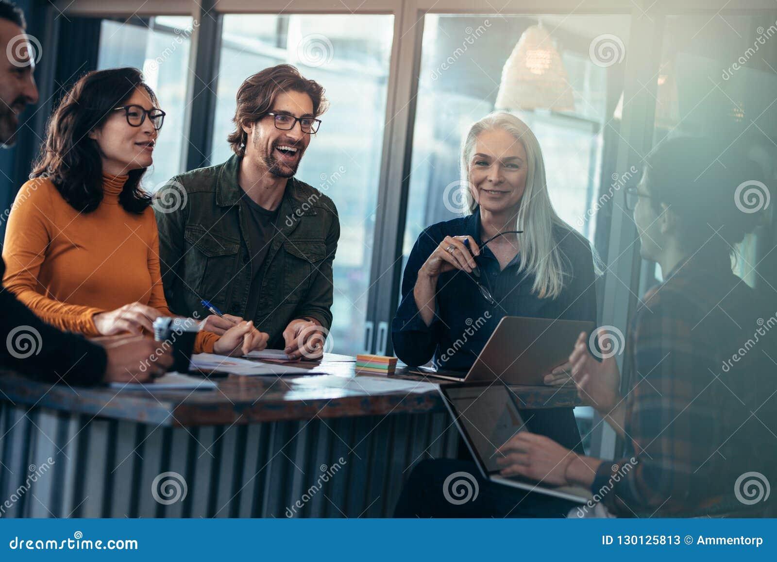 Szczęśliwy grupa ludzi ma spotkania w biurze