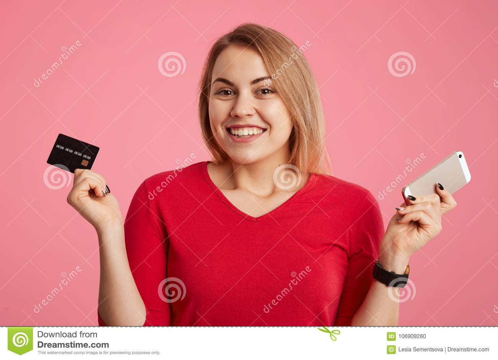 Szczęśliwy kobieta model raduje się dostawać pensję, trzyma klingeryt kartę i nowożytny mądrze telefon, iść weryfikować równowagę