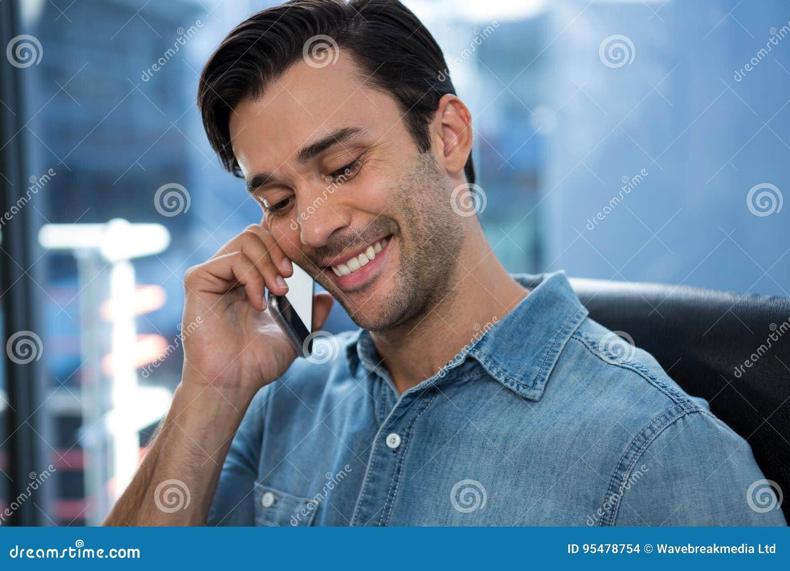 Szczęśliwy mężczyzna opowiada na telefonie komórkowym