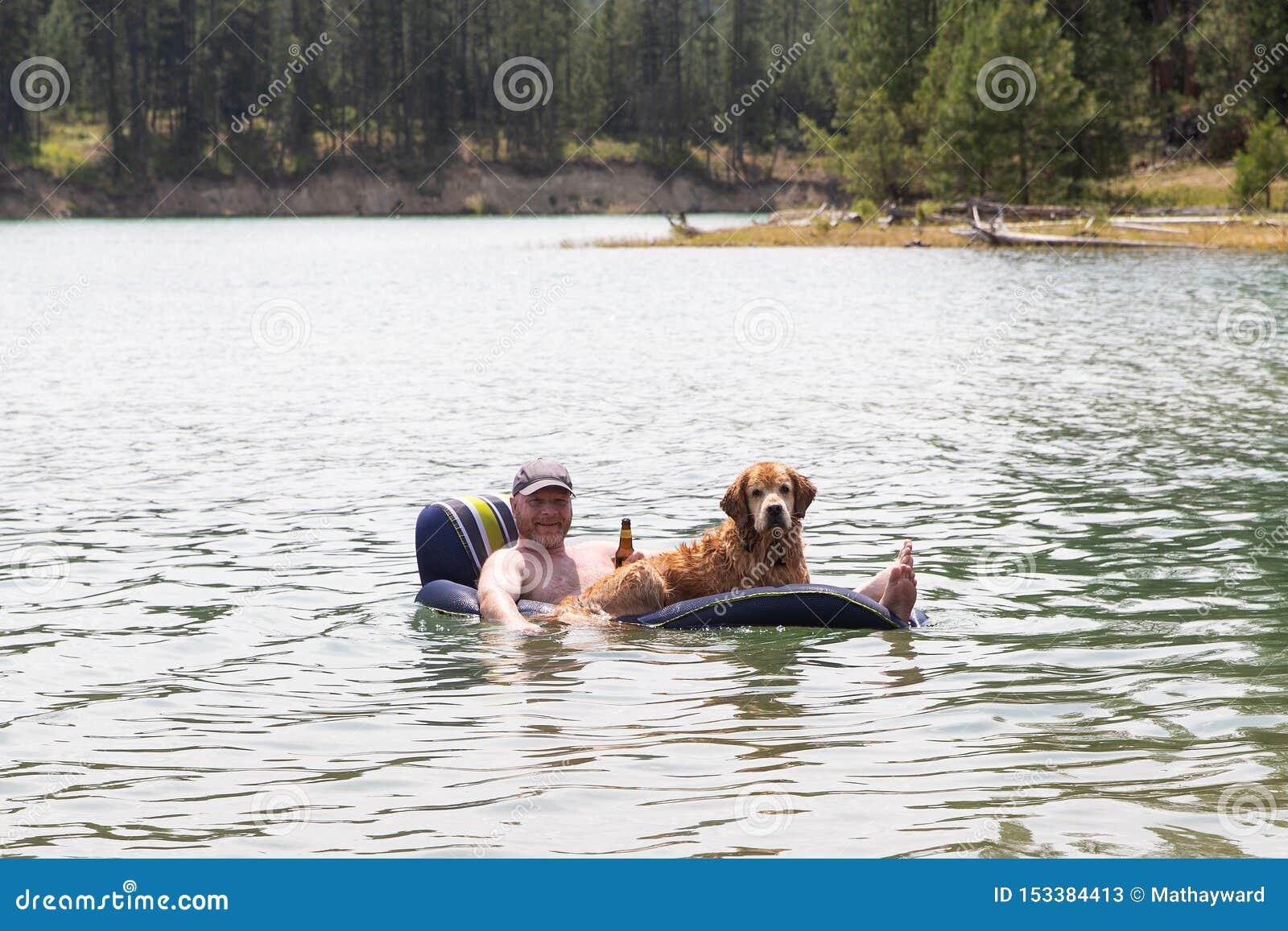 Szczęśliwy mężczyzna pije piwo i unosi się na jeziorze z jego golden retriever psem
