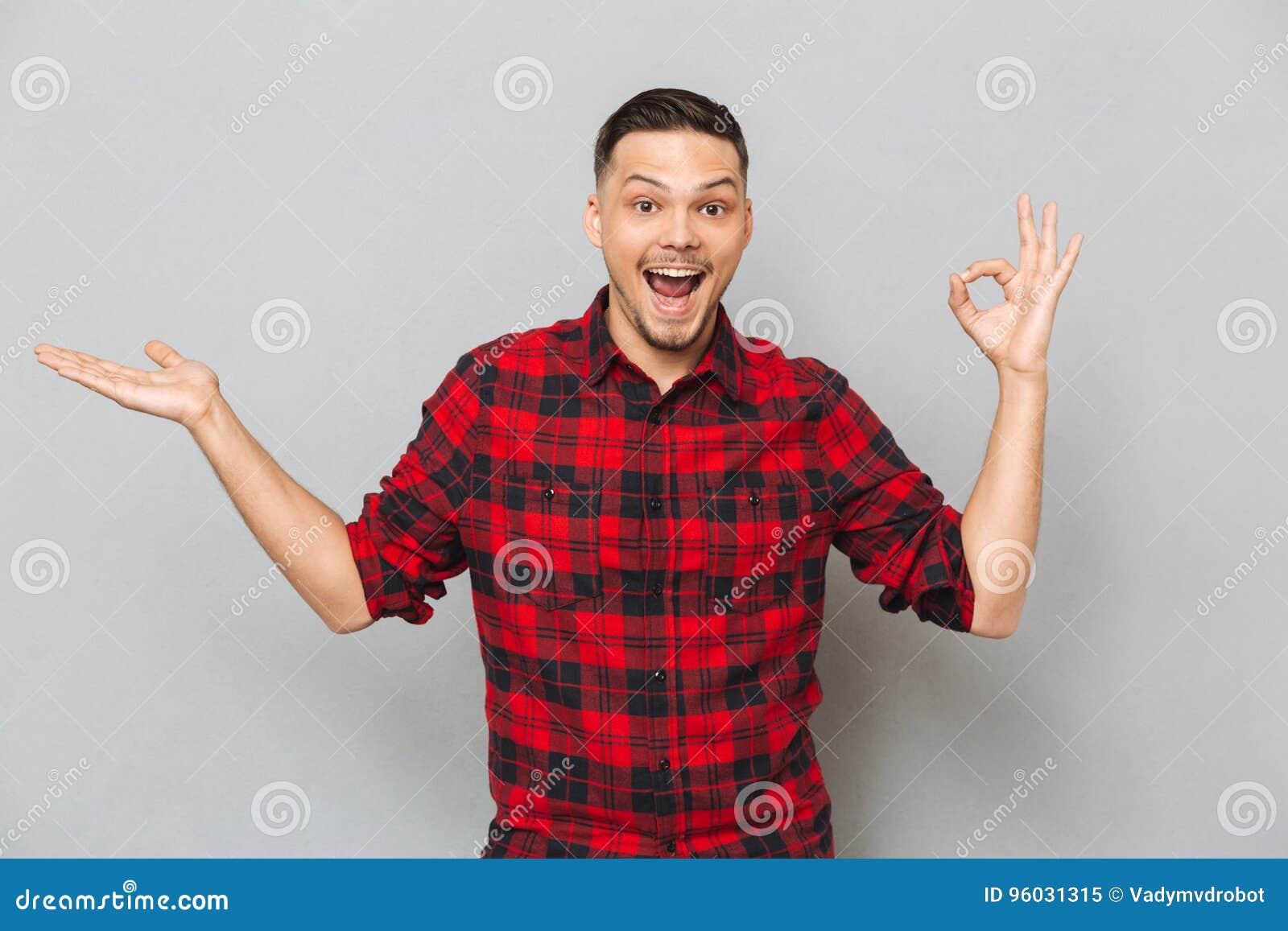 Szczęśliwy mężczyzna pokazuje ok znaka i trzyma copyspace na funcie