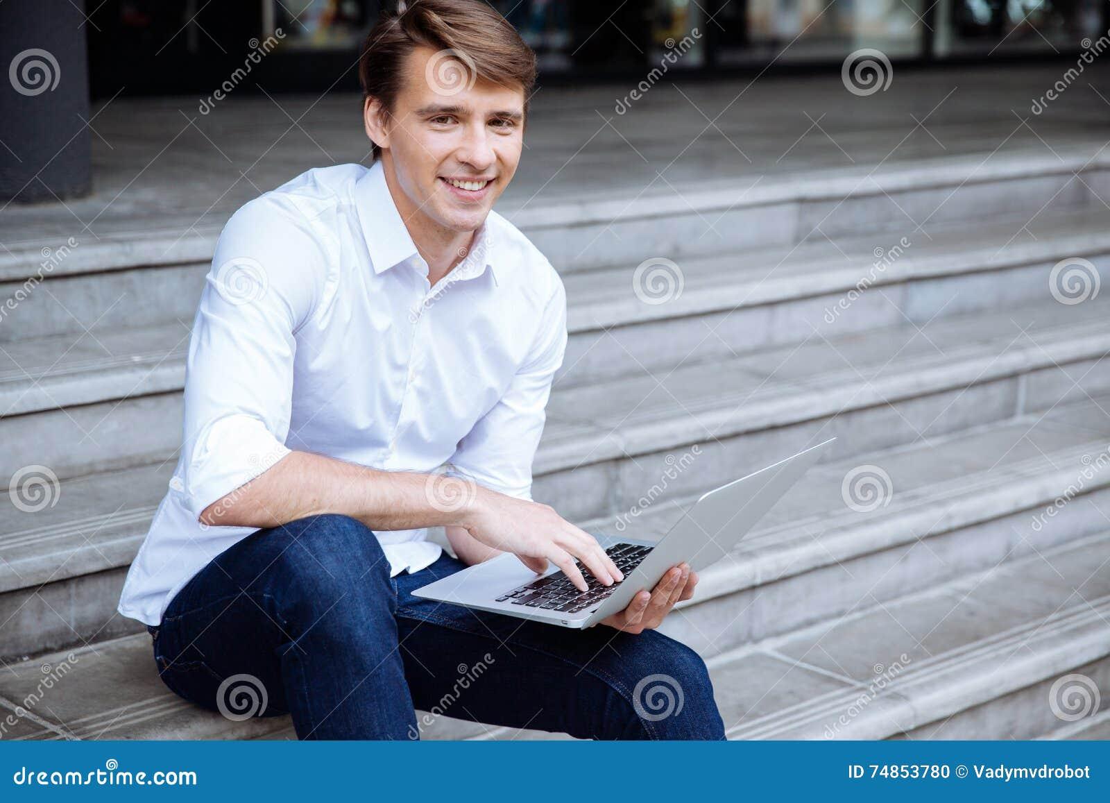 Szczęśliwy mężczyzna siedzi outdoors i używa laptop