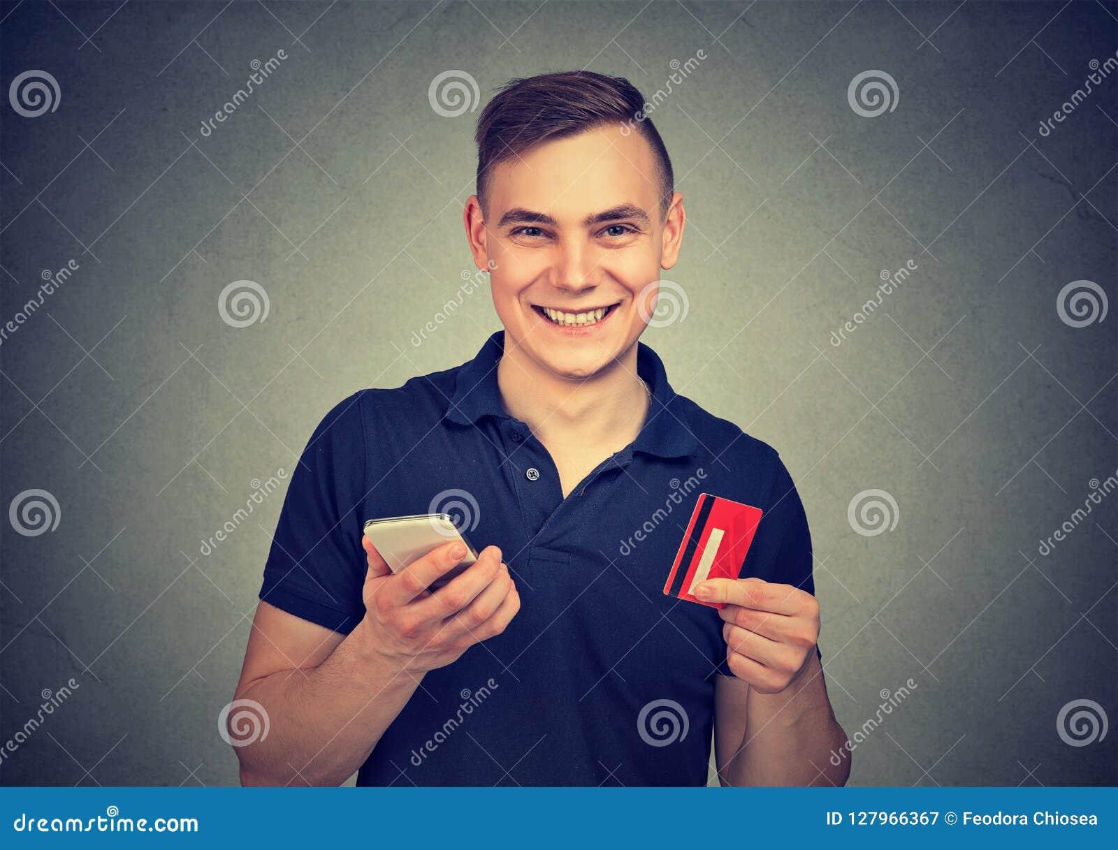 Szczęśliwy mężczyzna z smartphone i kredytową kartą