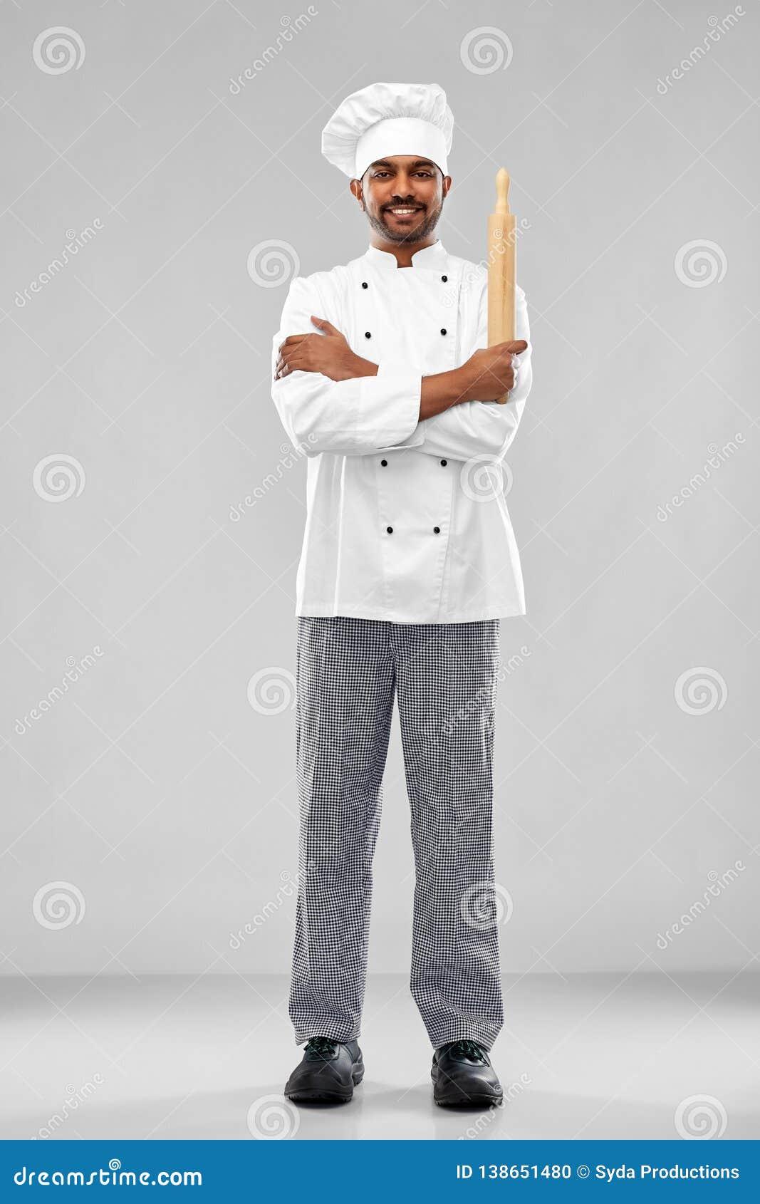 Szczęśliwy męski indyjski szef kuchni lub piekarz z wałkownicą