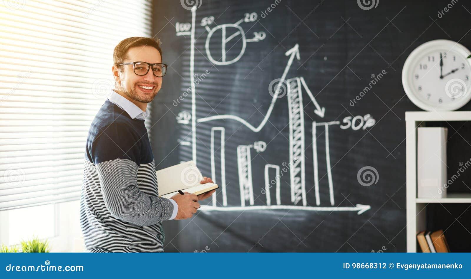Szczęśliwy męski uczeń, nauczyciel, freelancer z kredą przy blackboard