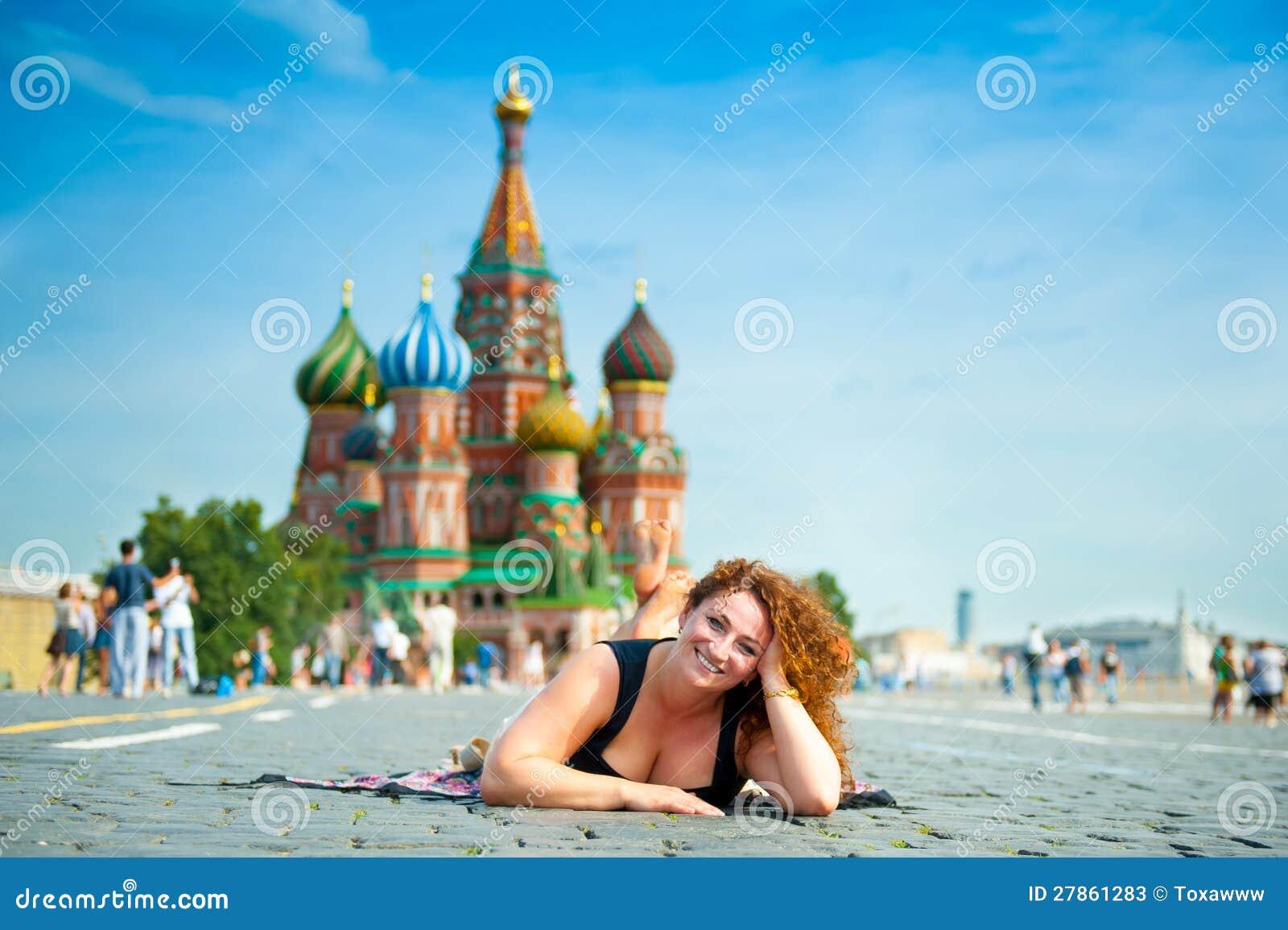 Szczęśliwy młodej kobiety lying on the beach na plac czerwony