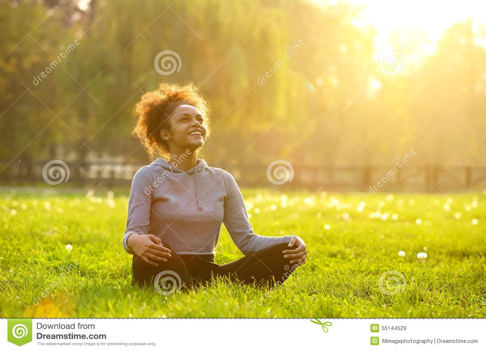 Szczęśliwy młodej kobiety obsiadanie w joga pozyci