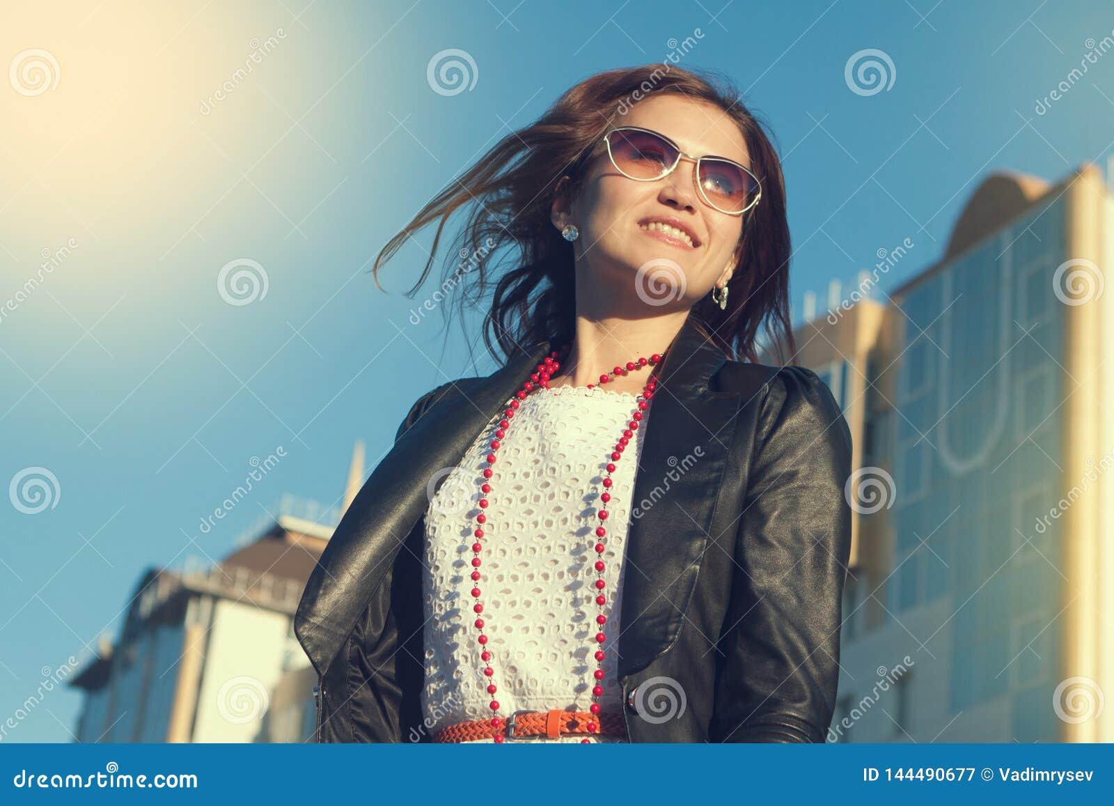 Szczęśliwy młodej kobiety odprowadzenie na miasto ulicie