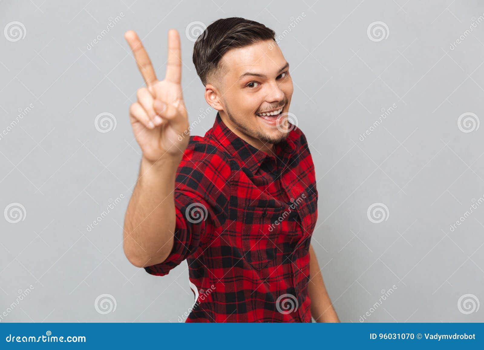 Szczęśliwy młody człowiek patrzeje kamerę pokazuje pokoju gest