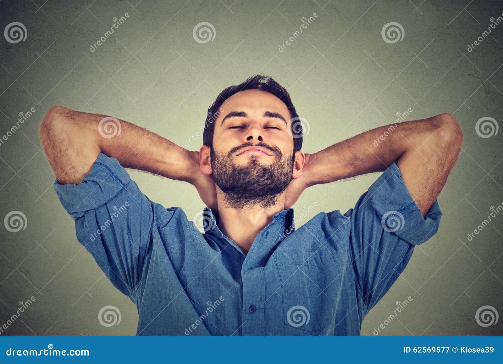 Szczęśliwy młody człowiek relaksuje lub drzema w błękitny koszulowy patrzeć upwards w myśli