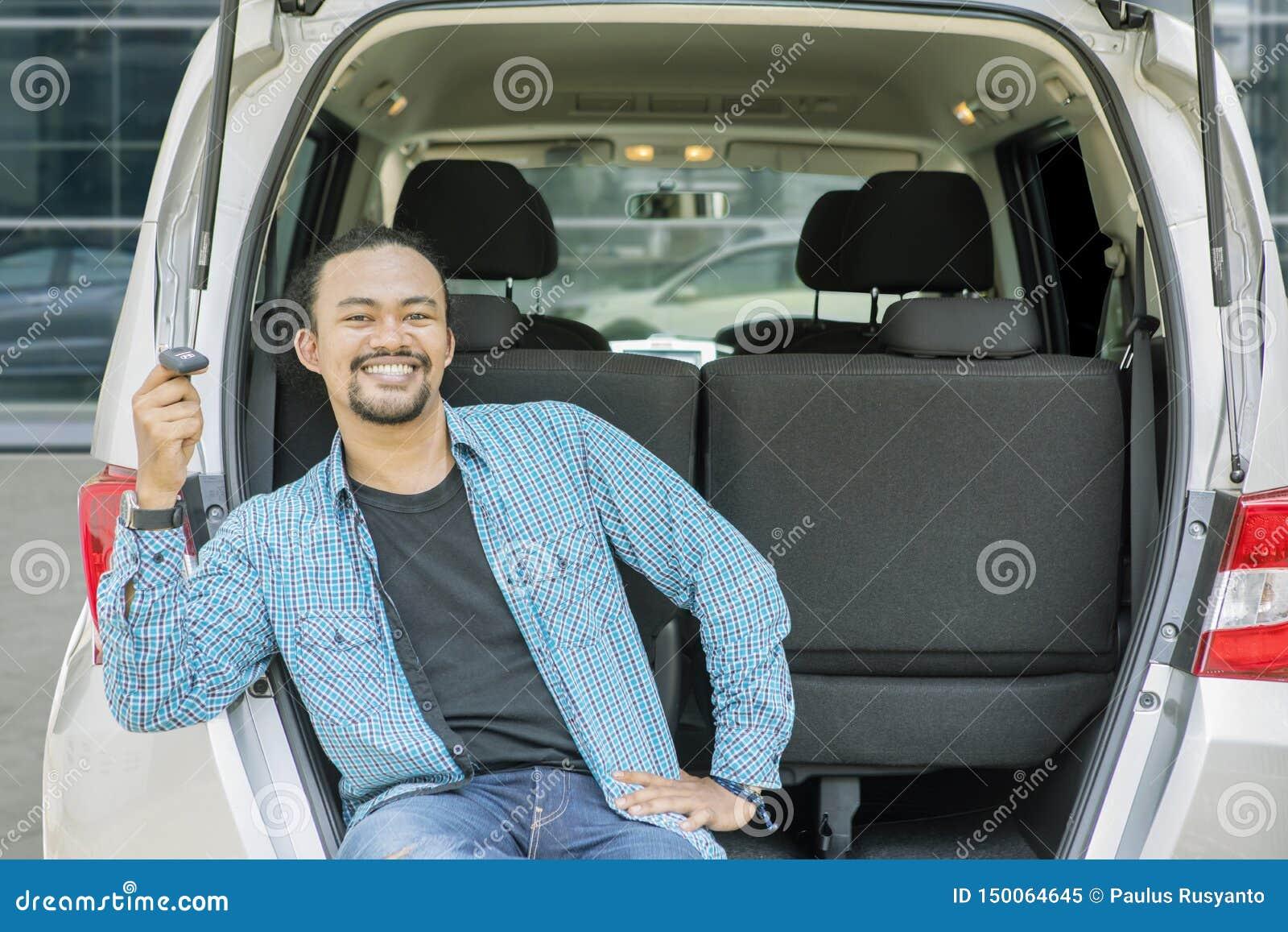 Szczęśliwy młody człowiek trzyma samochodowego klucz w samochodowym bagażniku