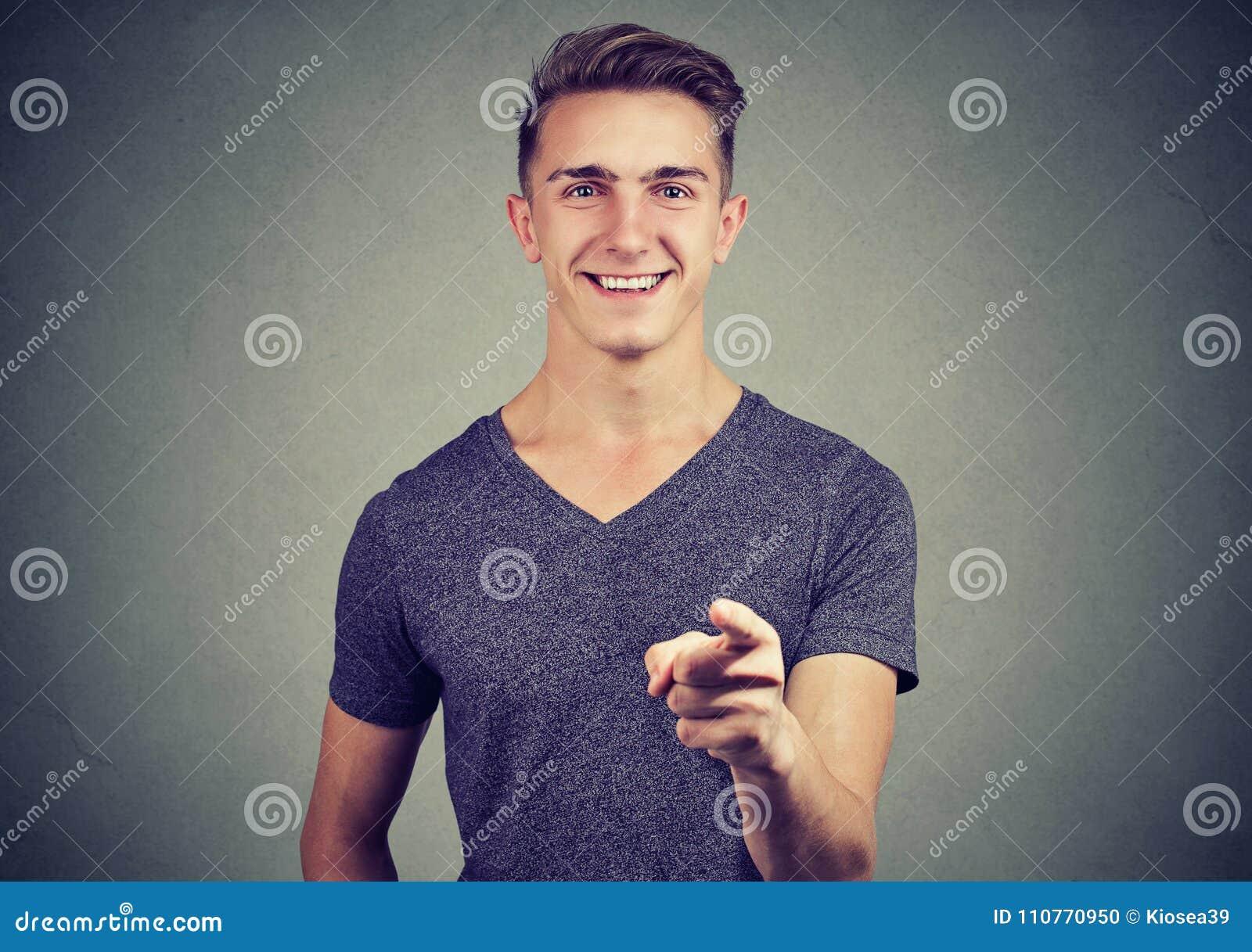 Szczęśliwy młody człowiek wskazuje jego palcowego przy tobą
