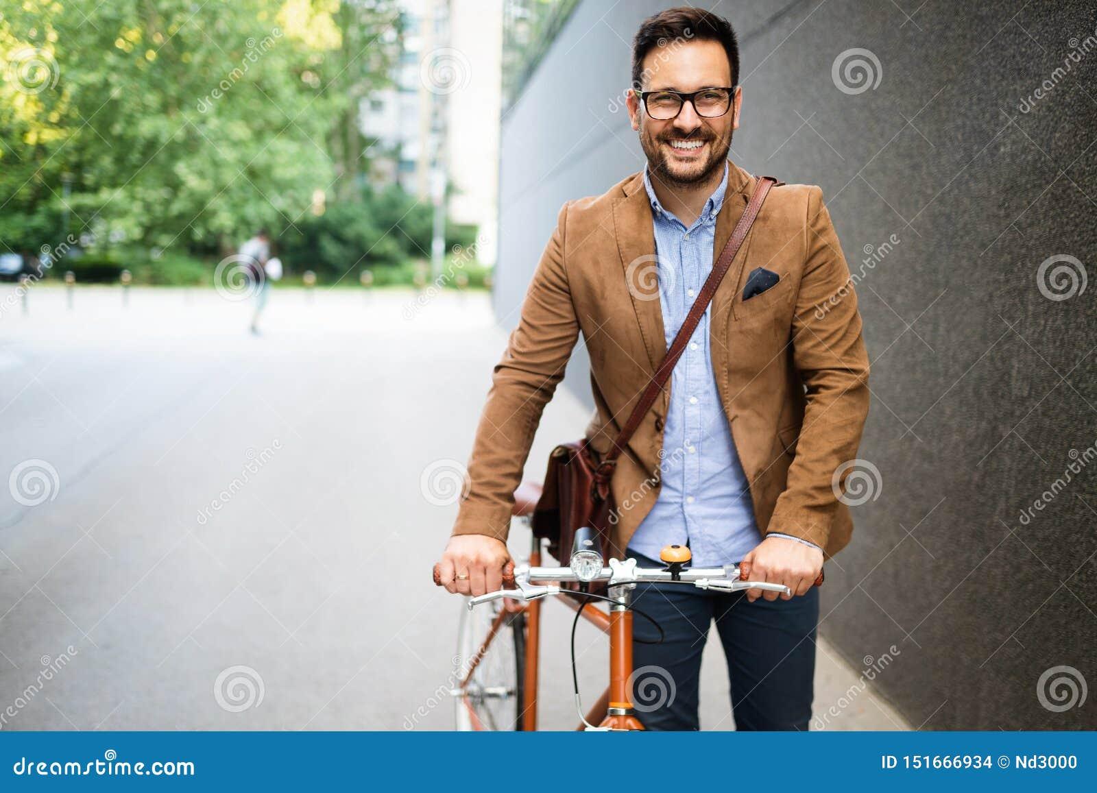 Szczęśliwy młody elegancki biznesmen iść pracować rowerem