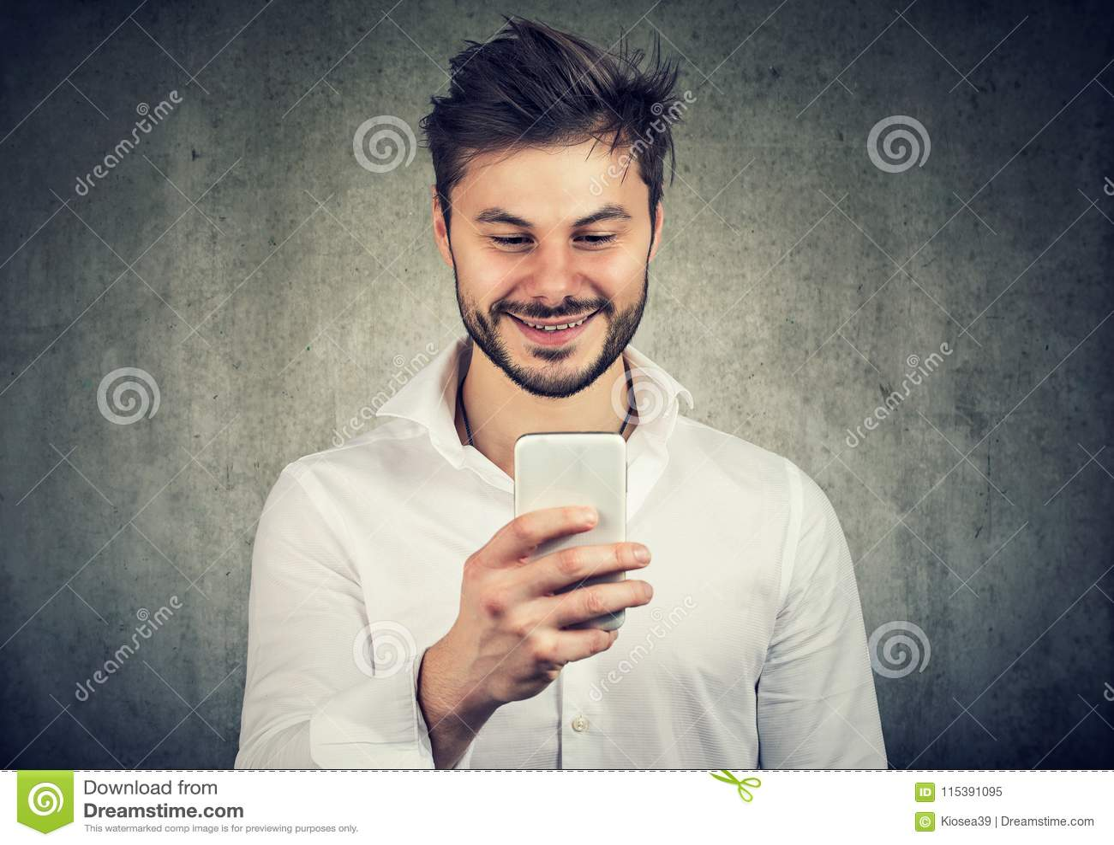 Szczęśliwy młody faceta dopatrywania smartphone