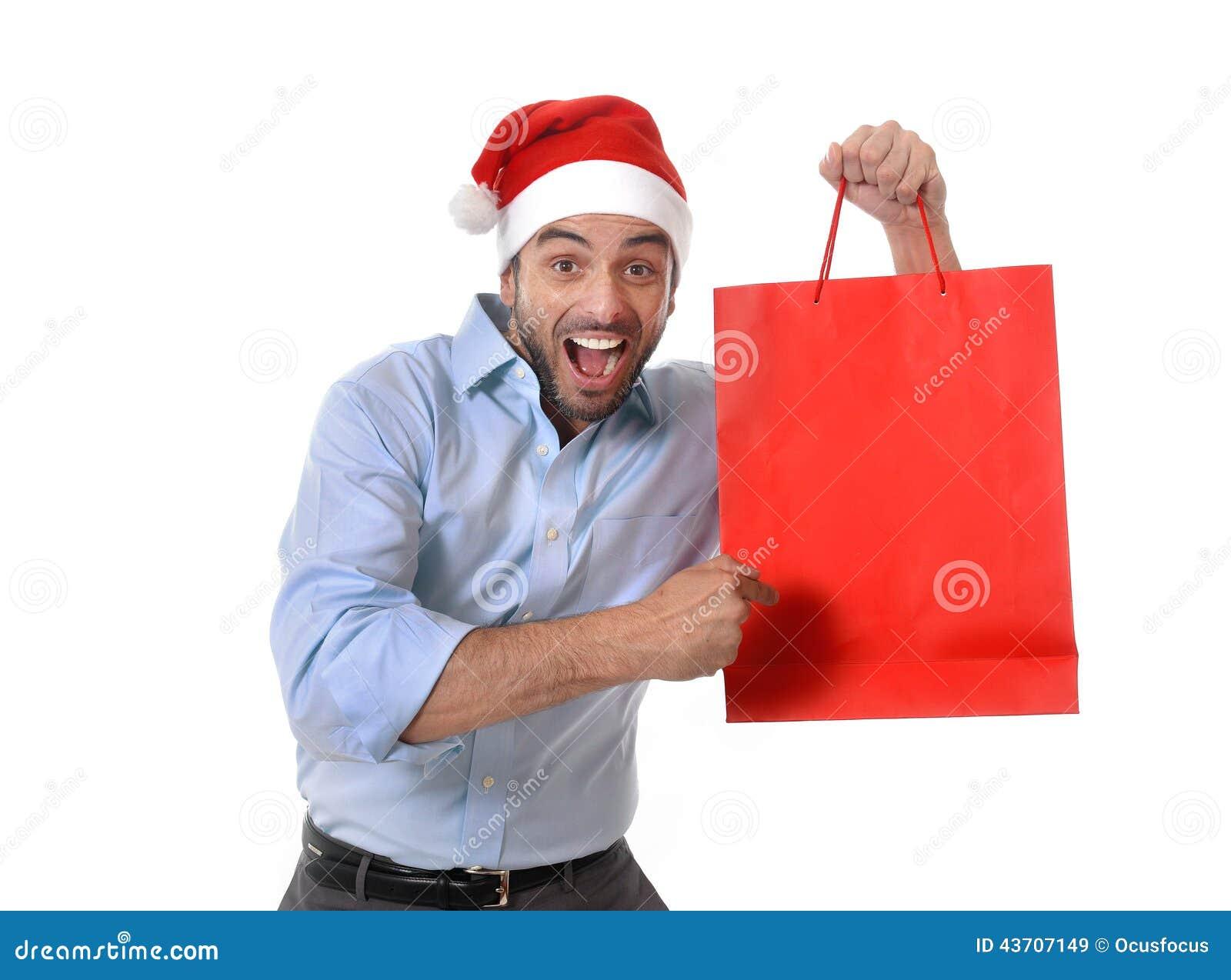 Szczęśliwy młody przystojny mężczyzna jest ubranym Santa mienia czerwieni kapeluszowego torba na zakupy