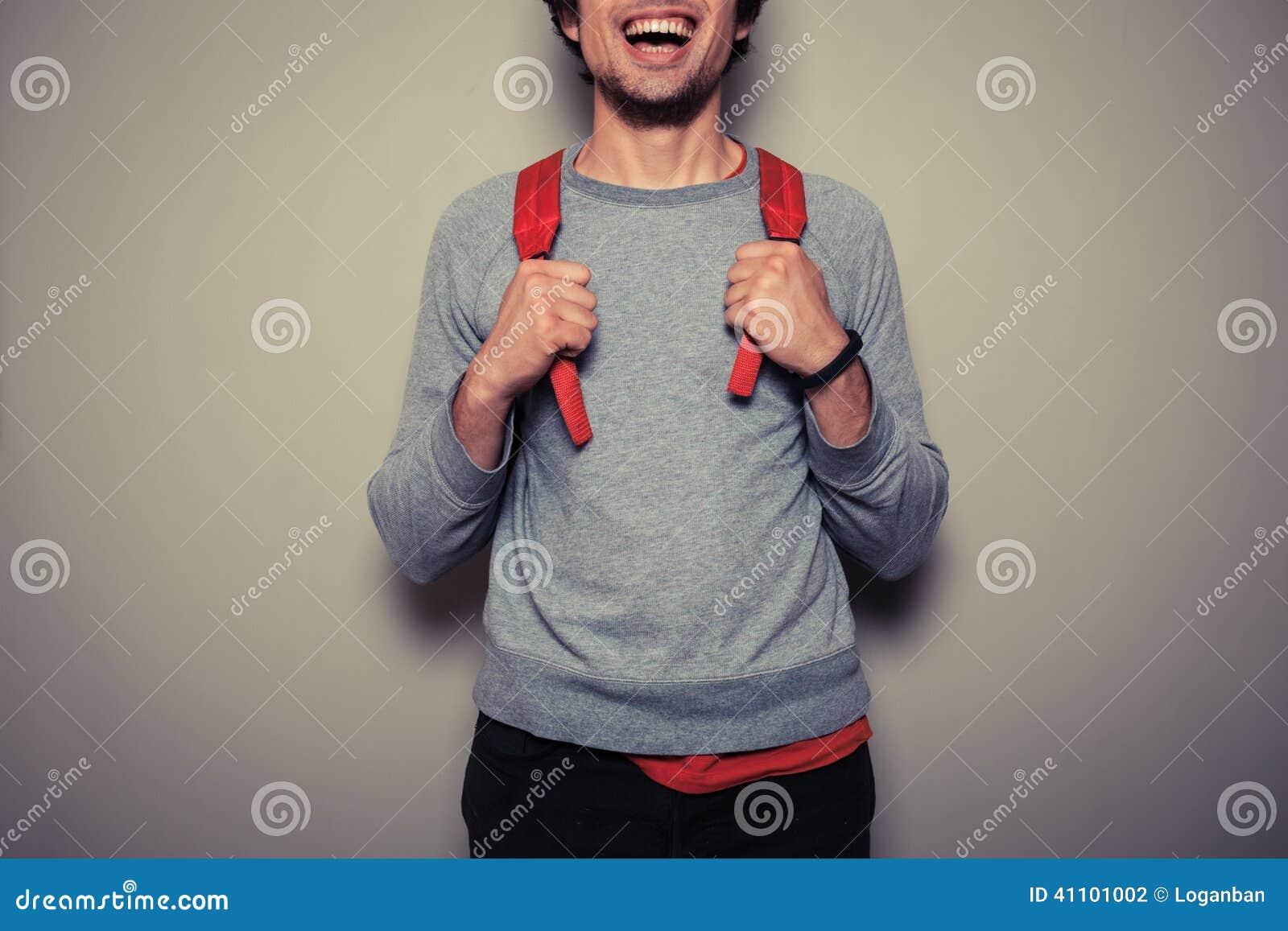 Szczęśliwy młody uczeń z czerwonym plecakiem