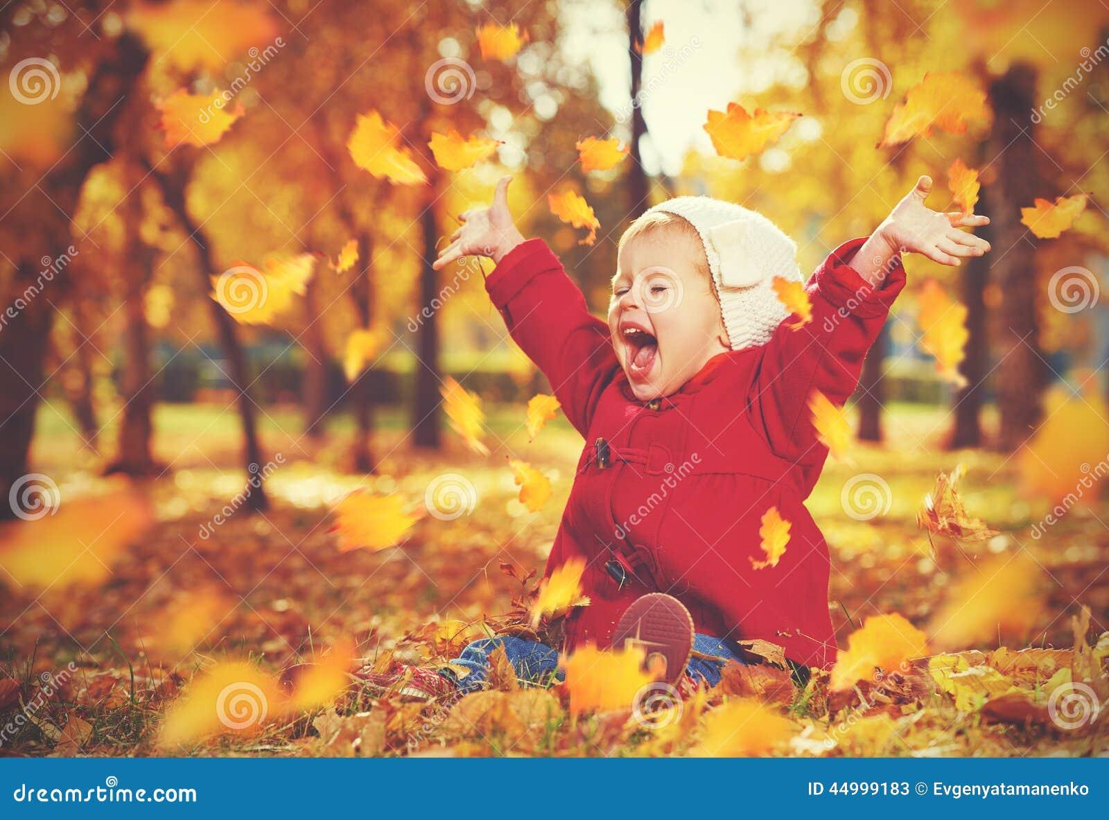 Szczęśliwy małe dziecko, dziewczynka śmia się i bawić się w jesieni