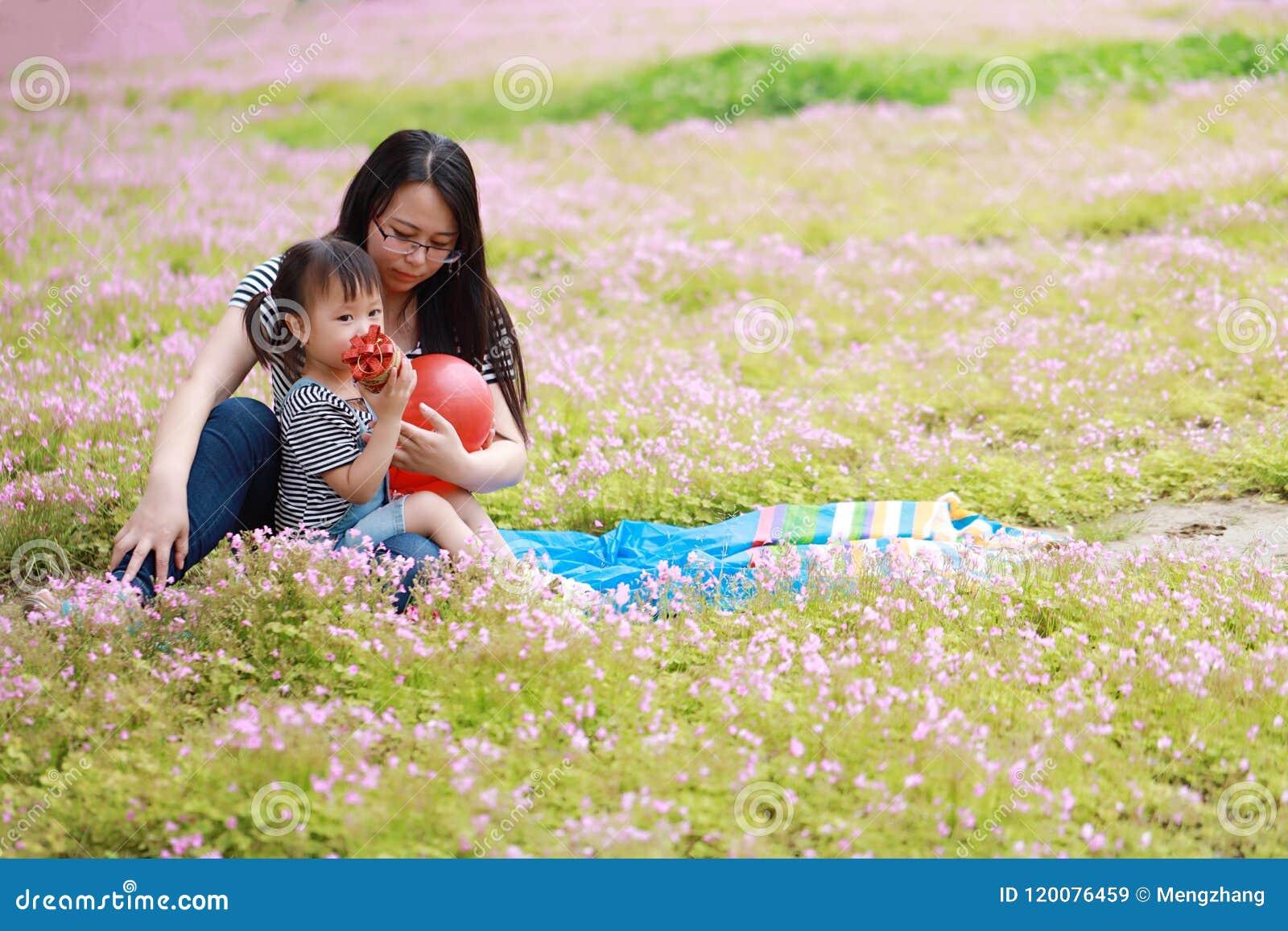 Szczęśliwy mały śliczny dziewczynka uśmiech, sztuka i szybko się zwiększać z matką, mama mówimy opowieść jego córka w lato parka